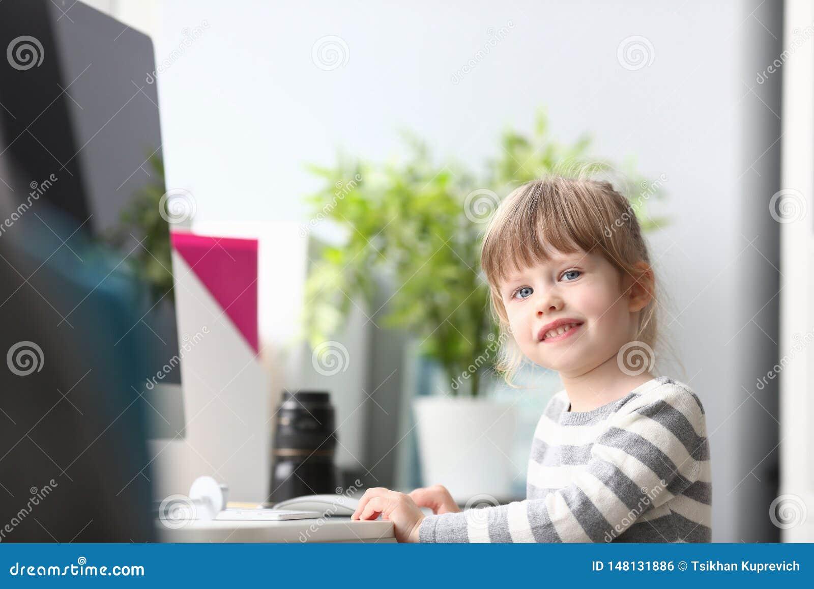 在家坐在工作台的逗人喜爱的女孩看在照相机