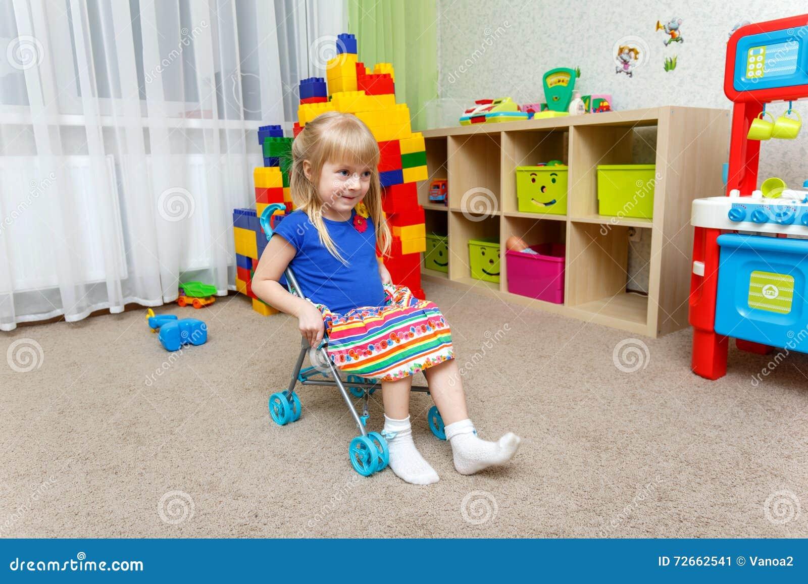 在家坐在玩具婴儿推车的微笑的小女孩
