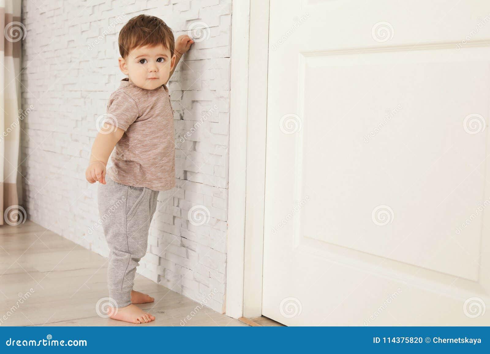 在家坚持墙壁的逗人喜爱的婴孩