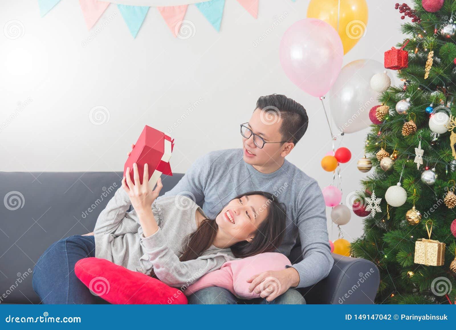 在家庆祝圣诞节的年轻夫妇 给他的女朋友礼物盒的帅哥
