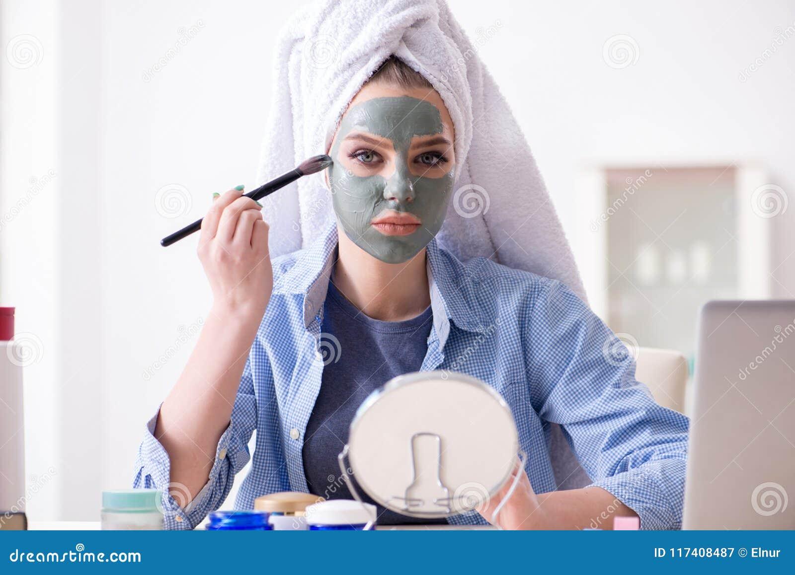 在家应用与刷子的妇女黏土面具