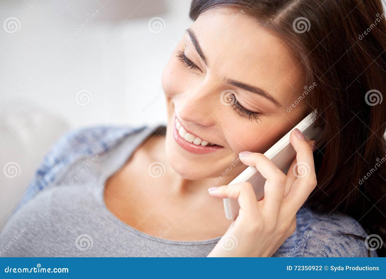 在家拜访智能手机的愉快的少妇