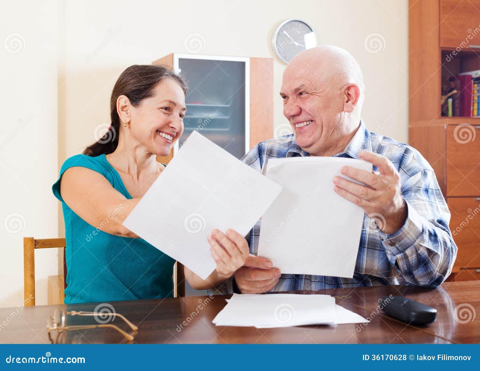 在家拿着文件的愉快的资深夫妇