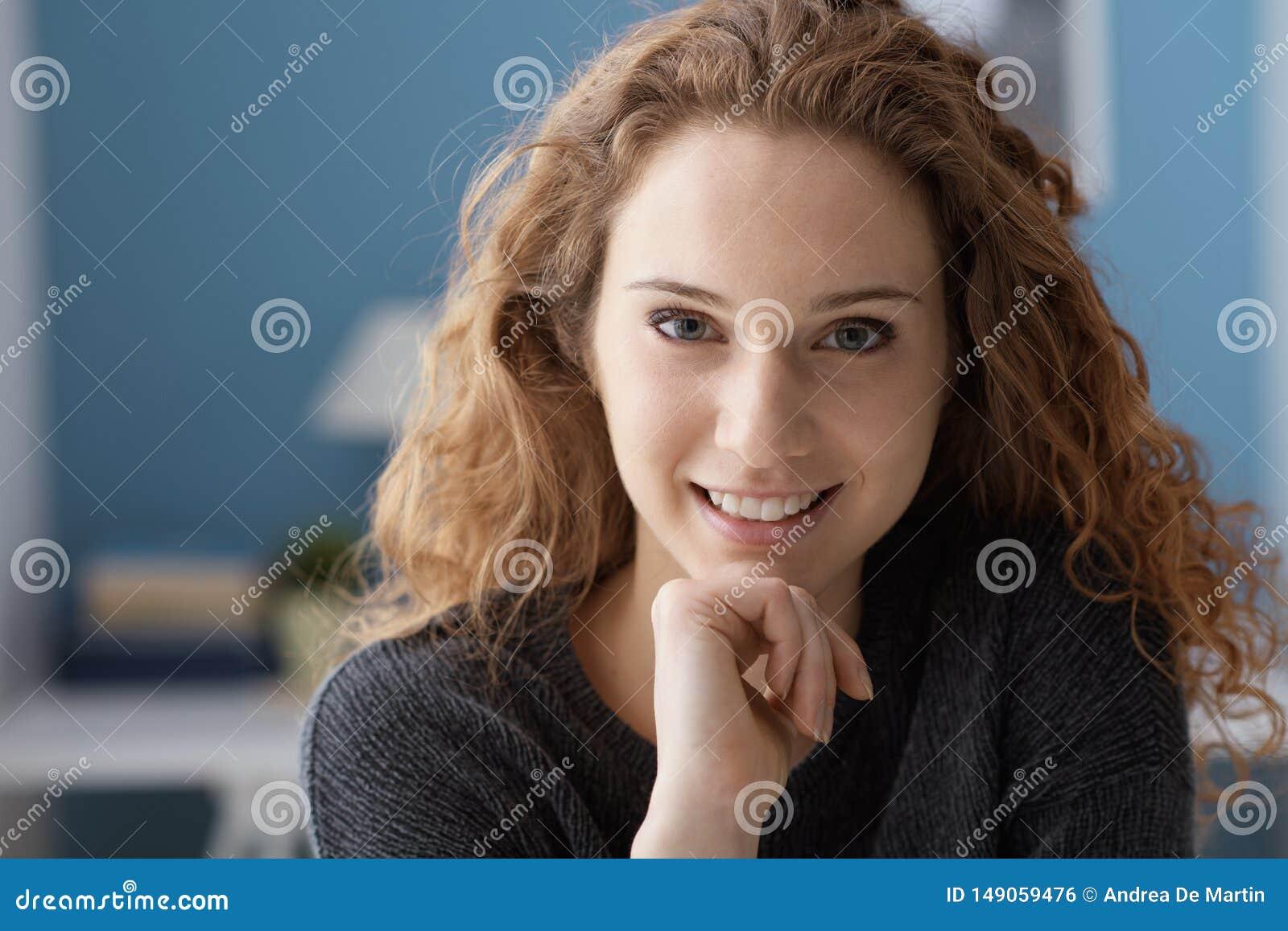 在家摆在美丽的卷曲的年轻女人