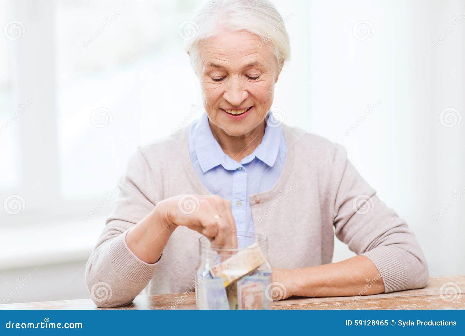 在家放金钱的资深妇女入玻璃瓶子
