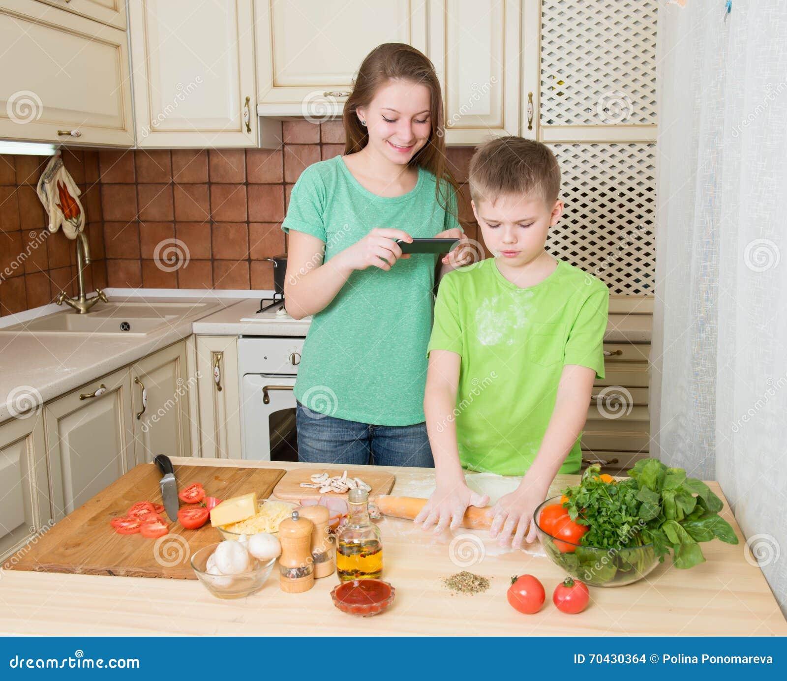 在家烹调自创薄饼厨房的愉快的孩子 少年