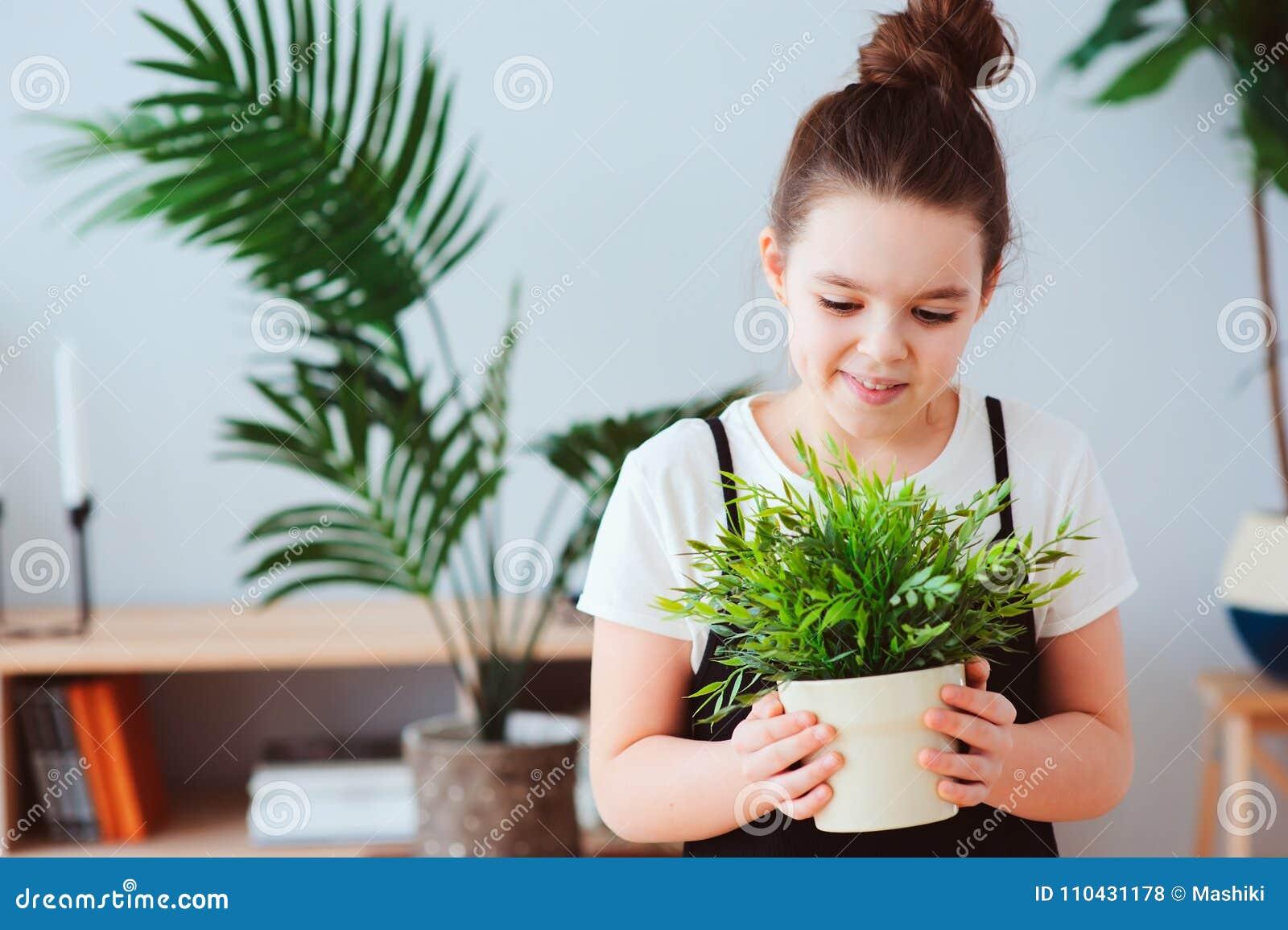 在家照顾室内植物的愉快的孩子女孩,穿戴在时髦的黑白成套装备