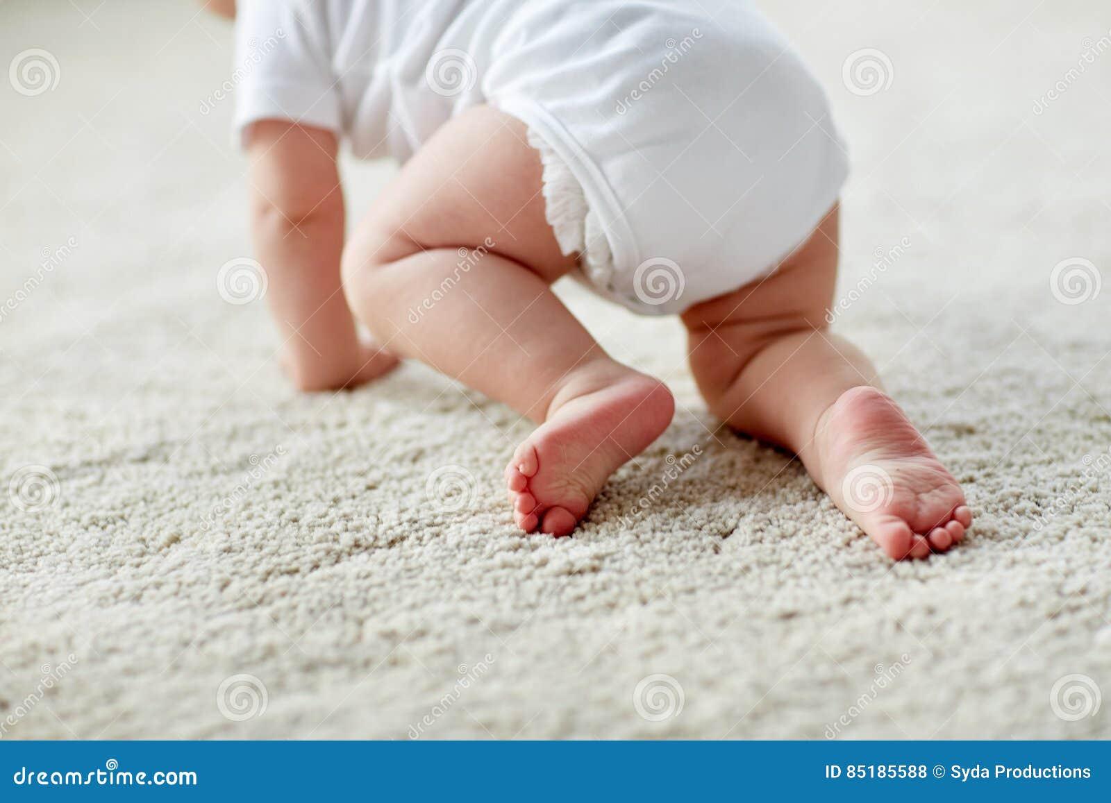 在家爬行在地板上的尿布的小婴孩