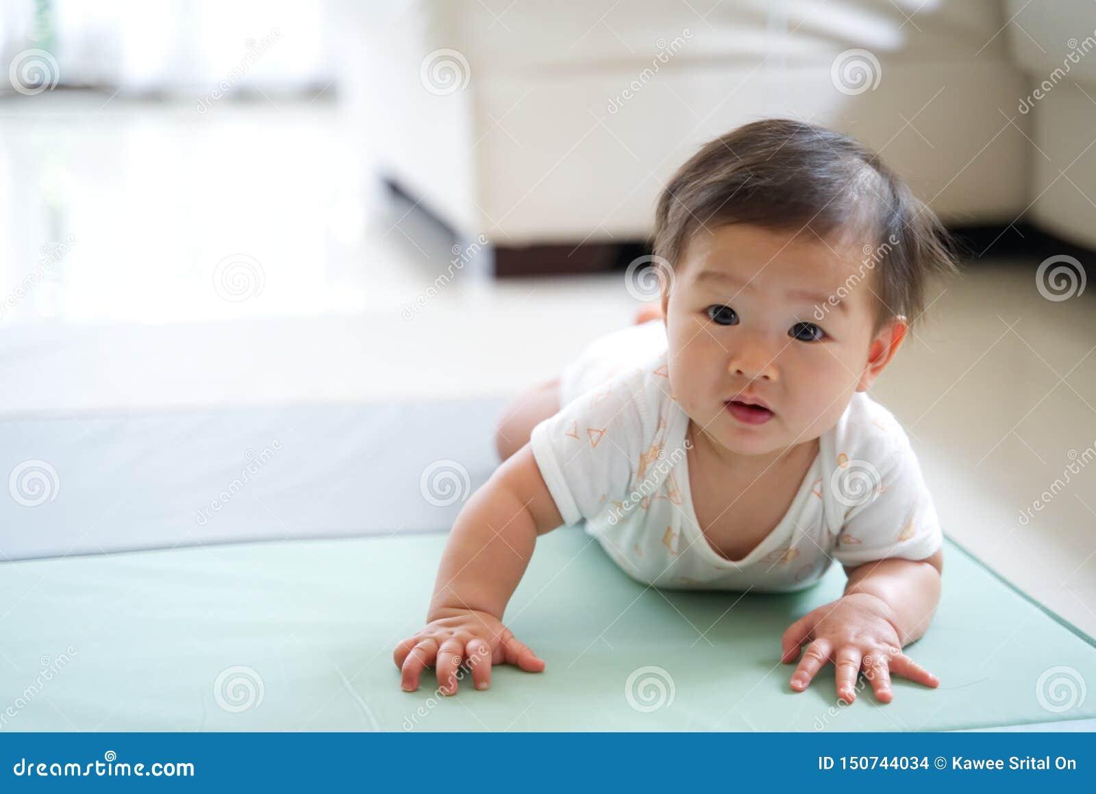 在家爬行在软的地毯或席子的亚裔可爱宝贝