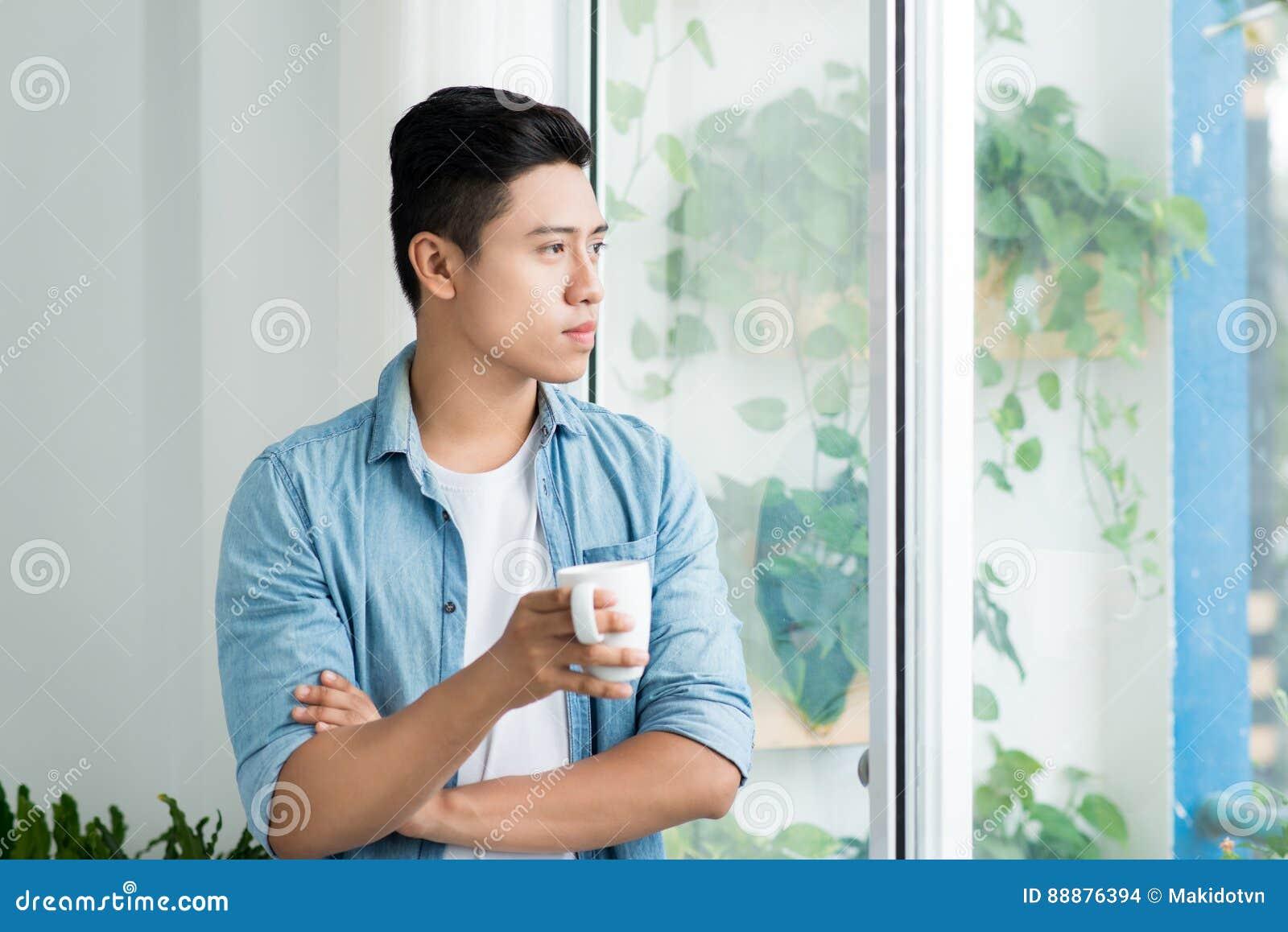 在家看窗口的体贴的亚裔人在卧室