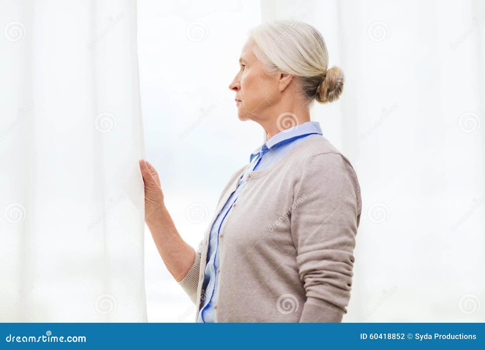 在家看通过窗口的孤独的资深妇女