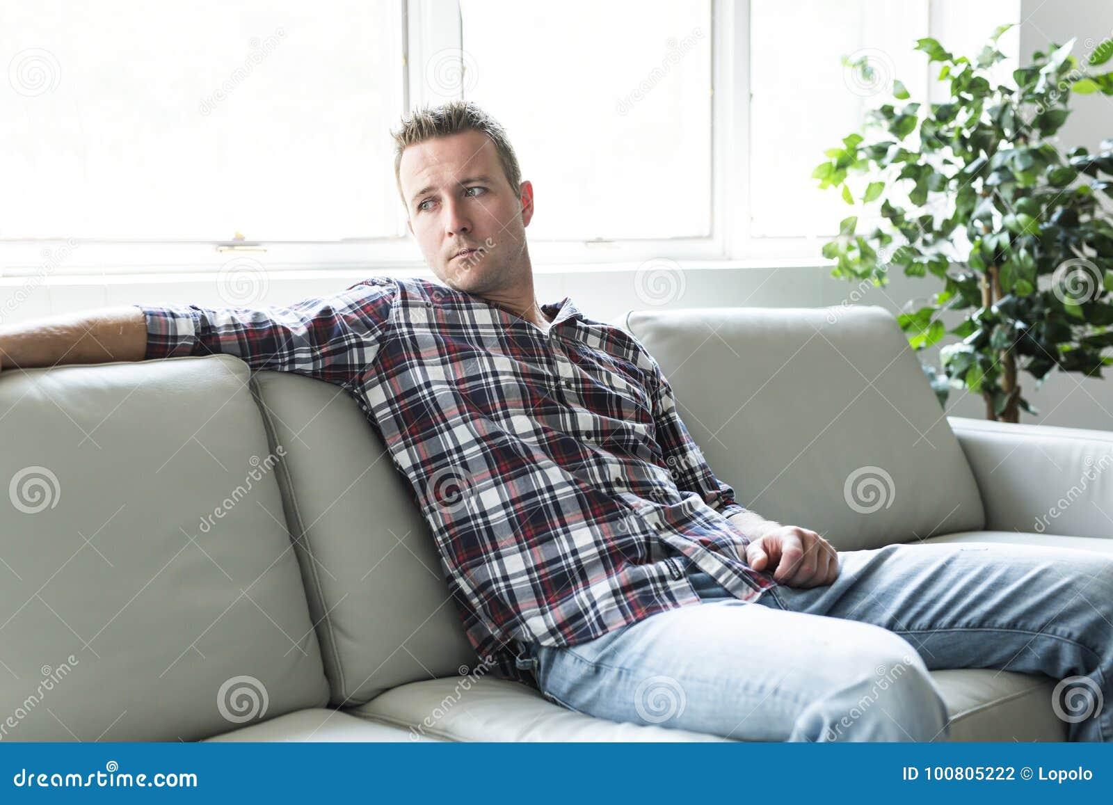 在家认为在单独沙发的沮丧的人