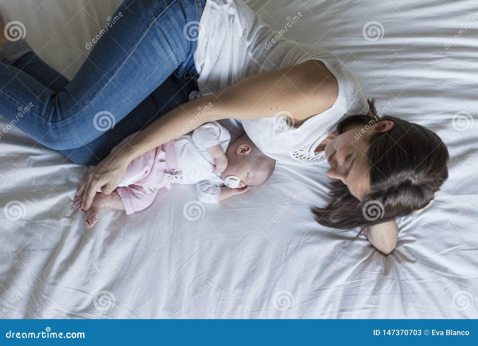 在家说谎在床上的年轻母亲与她的女婴 家庭和爱概念