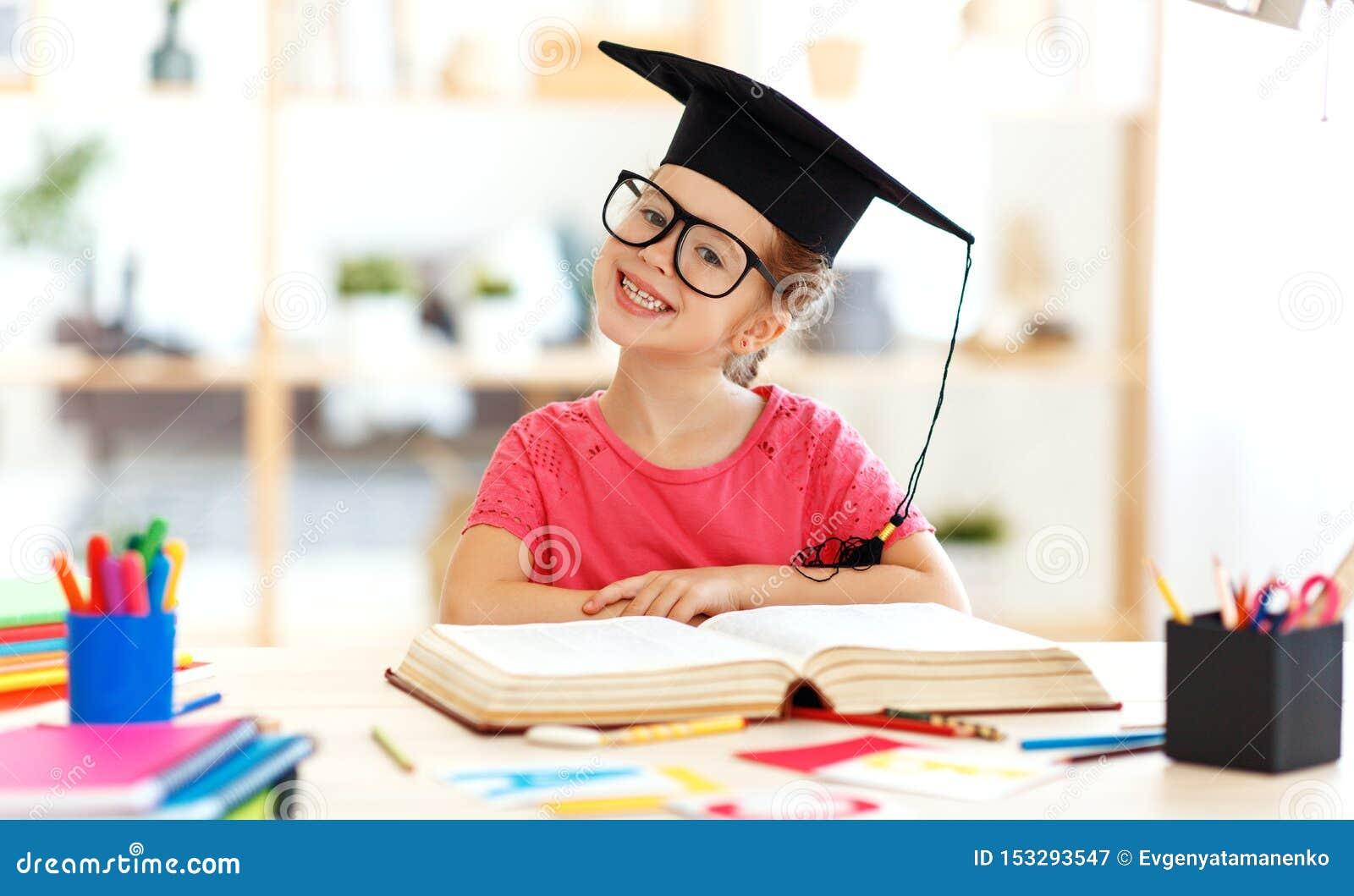 在家读滑稽的儿童的女孩做家庭作业文字和