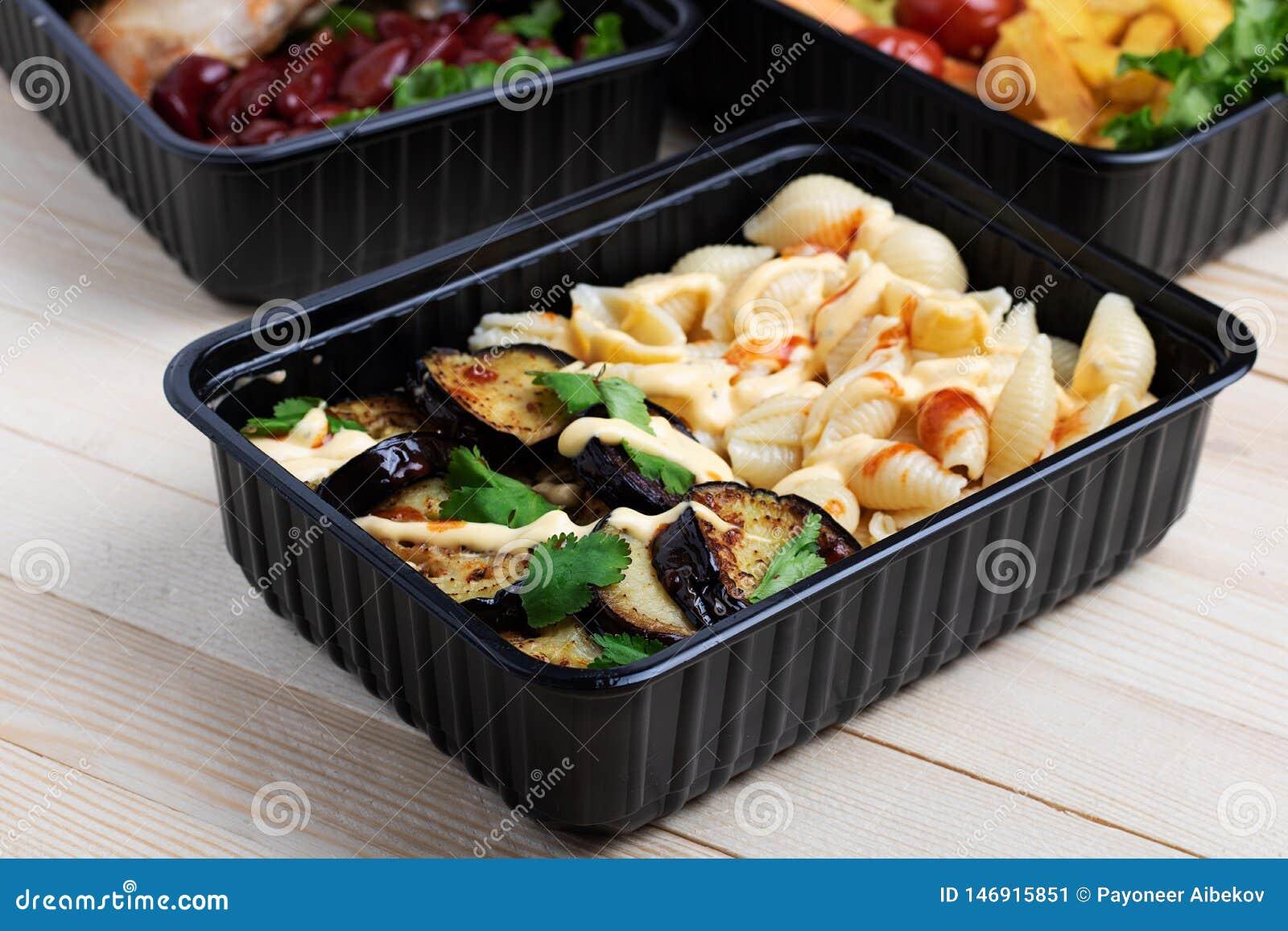 在容器的油煎的茄子有烤鸡翅和未加工的蔬菜的在土气背景、西红柿和微greenss