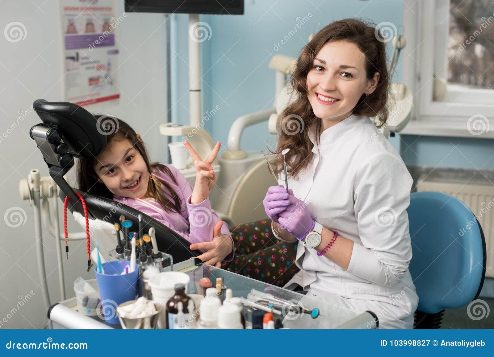 在对待牙以后的微笑的女性牙医和女孩患者在牙齿诊所办公室