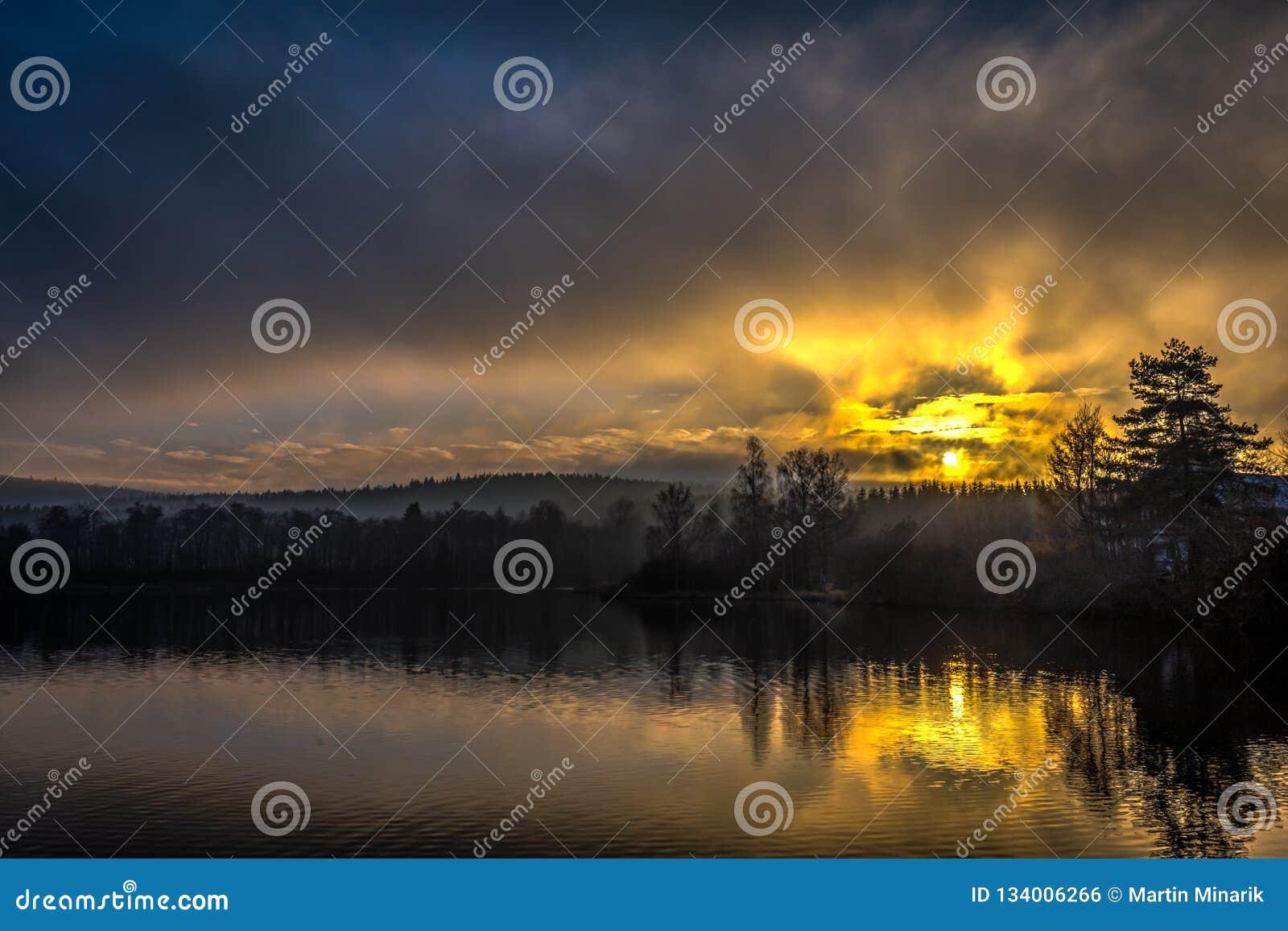 在小池塘的有薄雾的黄色和蓝色日落在捷克Moravian高地