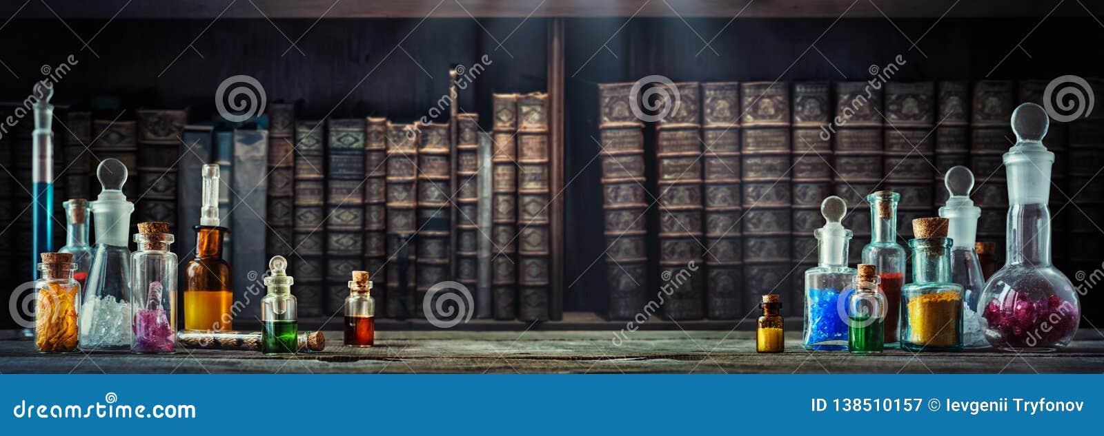 在小瓶的葡萄酒疗程在木书桌和旧书背景 老医疗,化学和药房历史概念