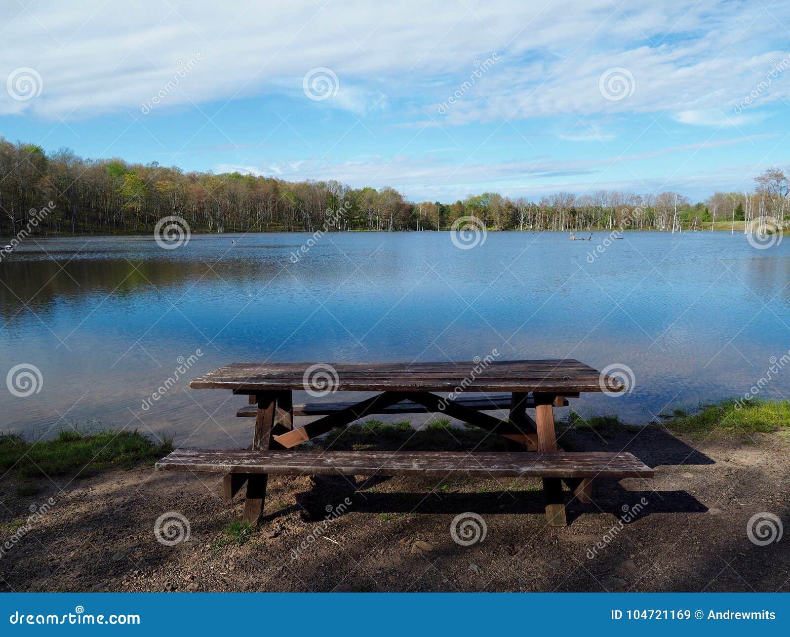 在山湖旁边的土气野餐桌