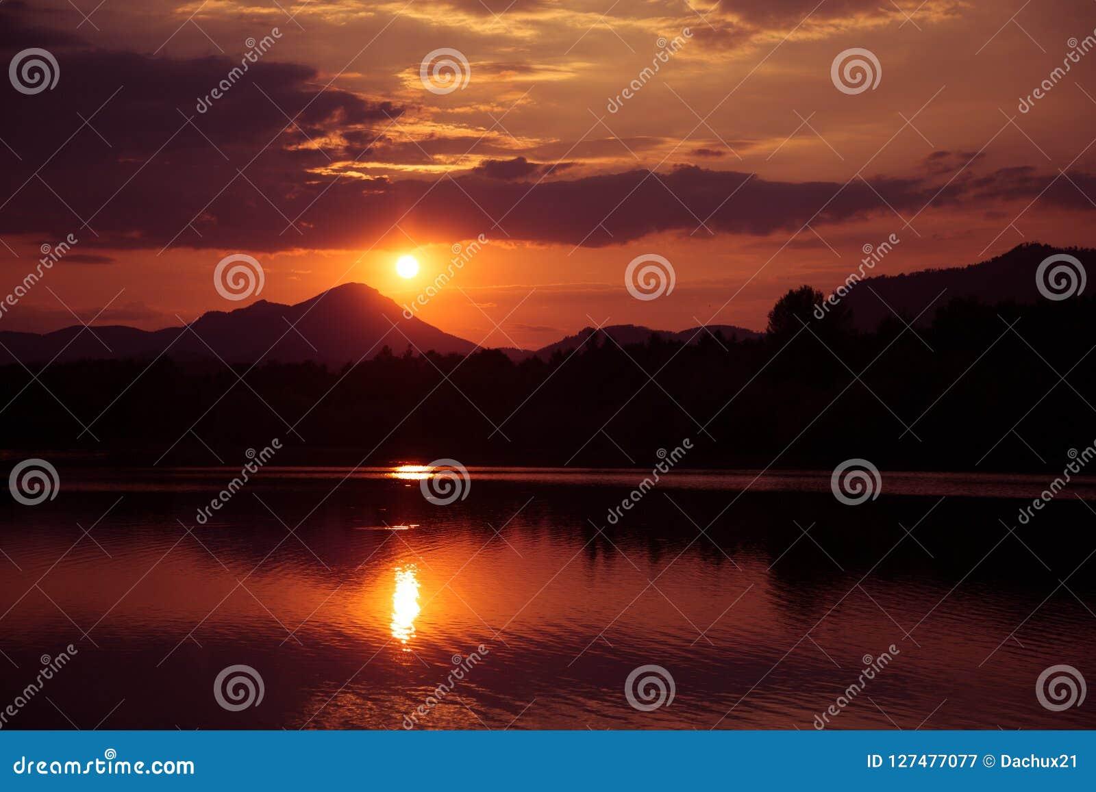 在山的一个美丽,五颜六色的日落,湖和森林紫色口气的 抽象,明亮的风景
