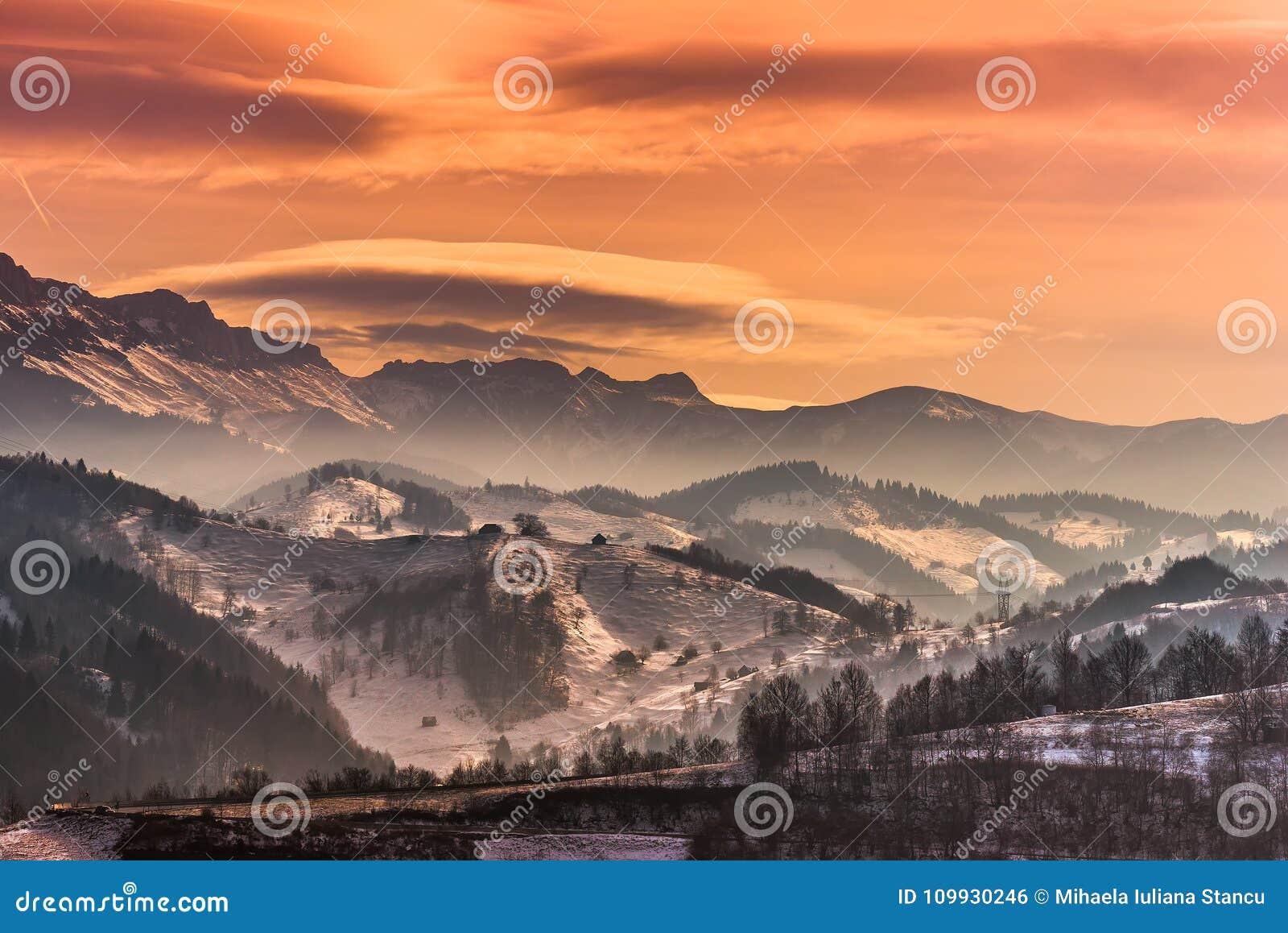 在山的美好的冬天在日落的风景与双突透镜的云彩和雪点燃
