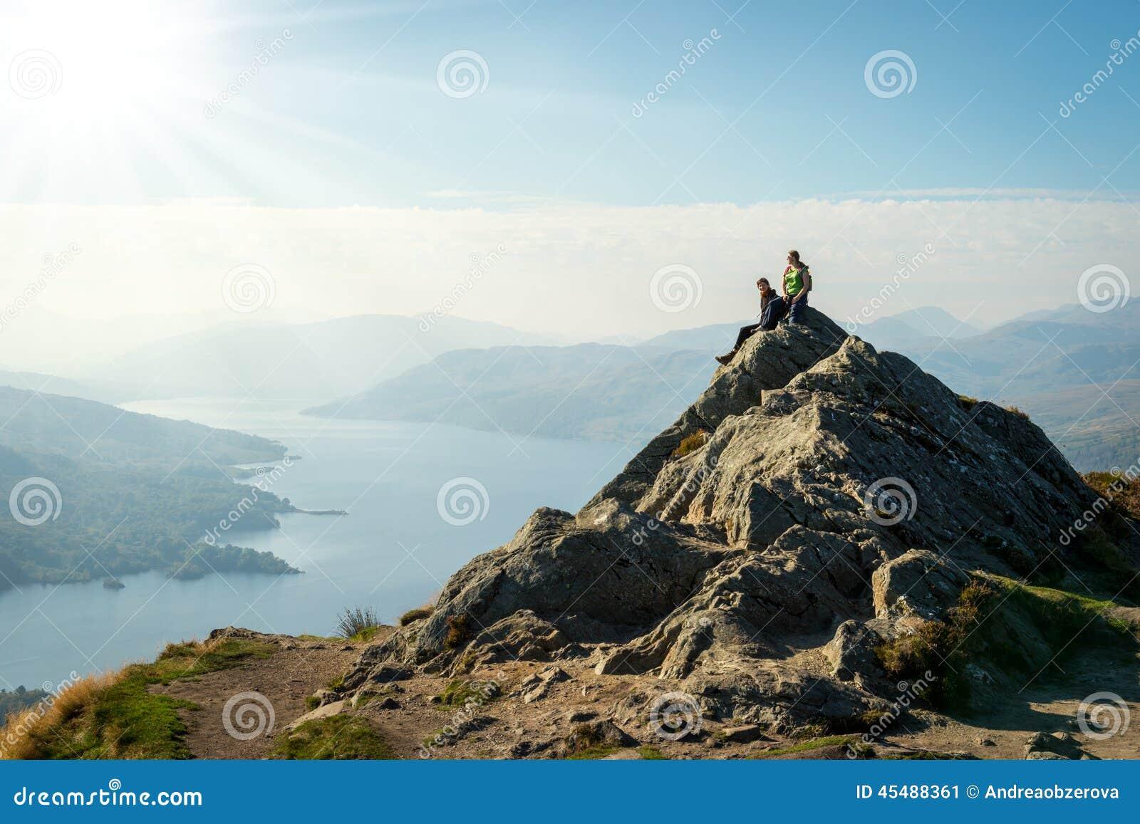在山顶部的女性远足者享受谷视图的