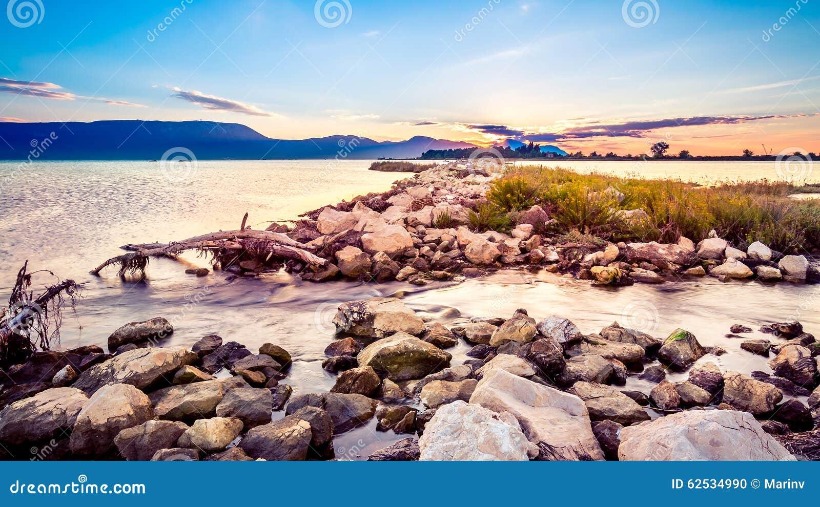 在岩石岸的美好的夏天日落由海