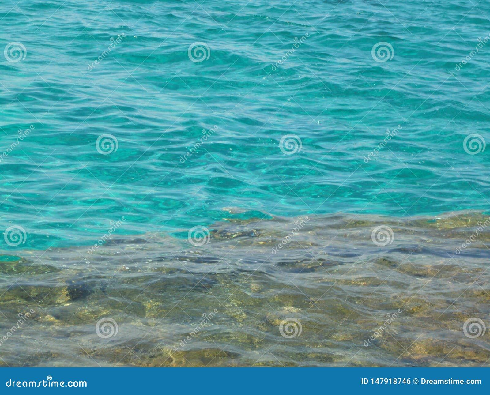 在岩石底部的透明的绿松石水