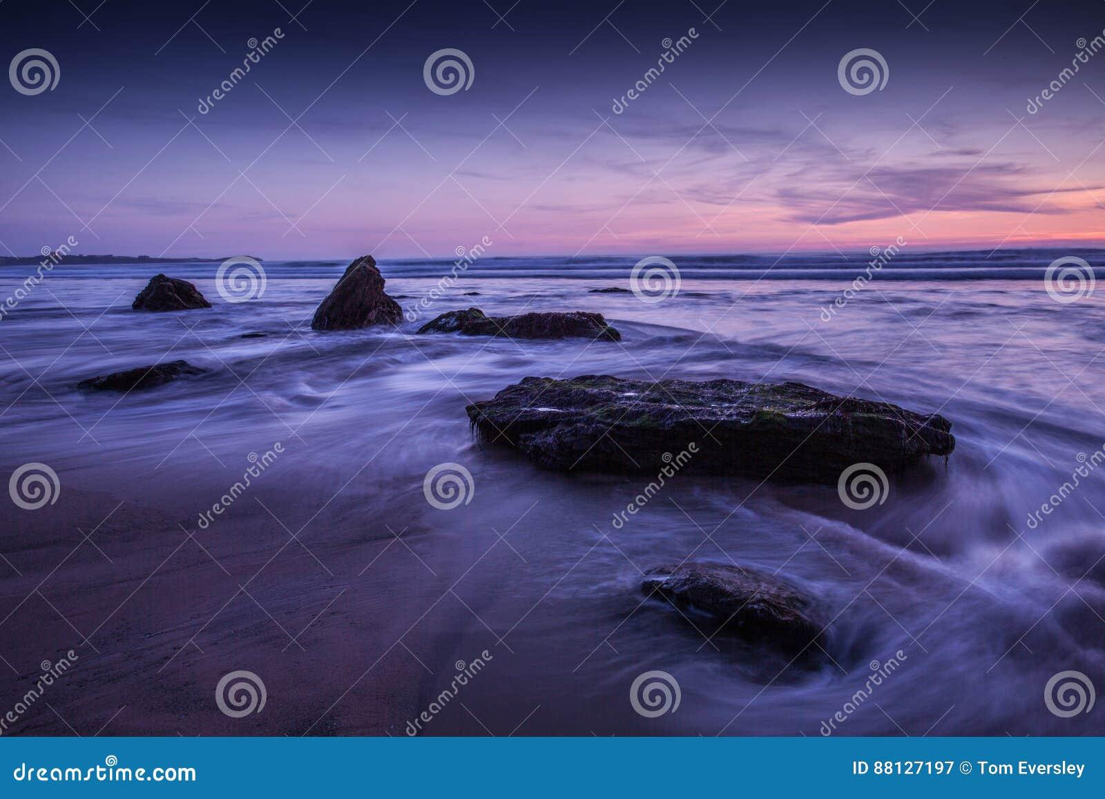 在岩石海洋海滩的紫色天空日落