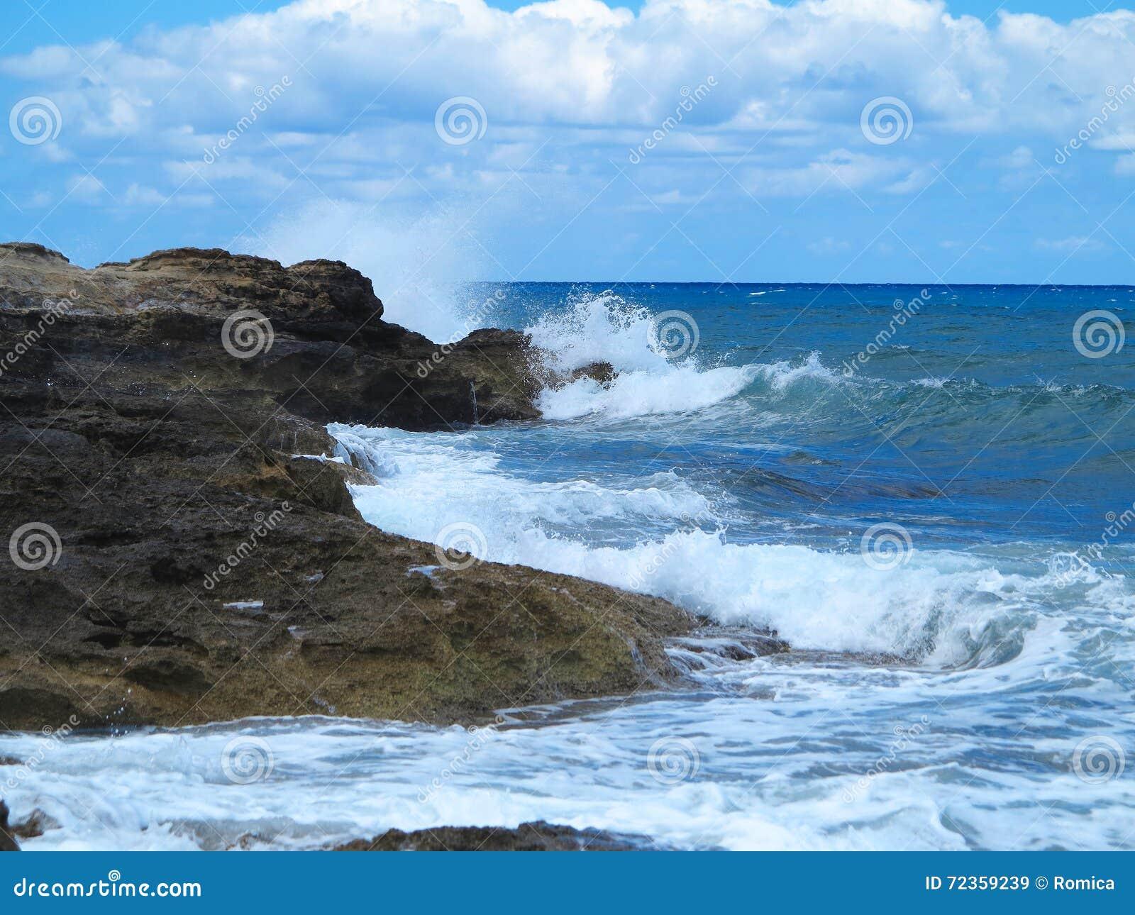 在岩石的大波浪沿岸航行蓝色海和天空在克利特