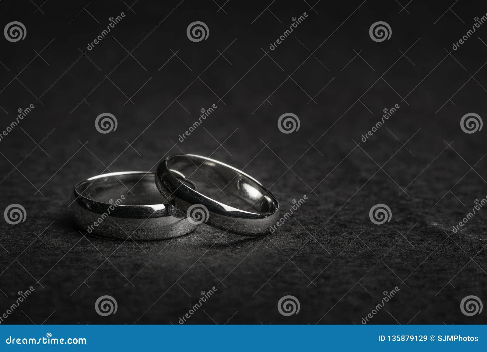 在岩石背景的银色结婚戒指