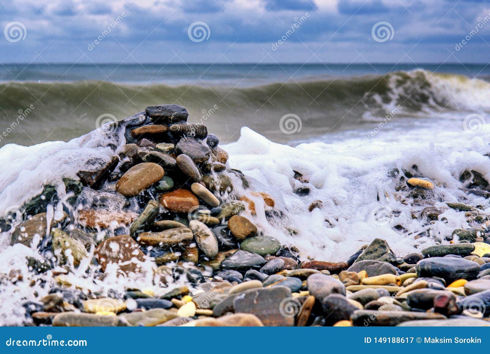 在岸的石头反对海波浪背景