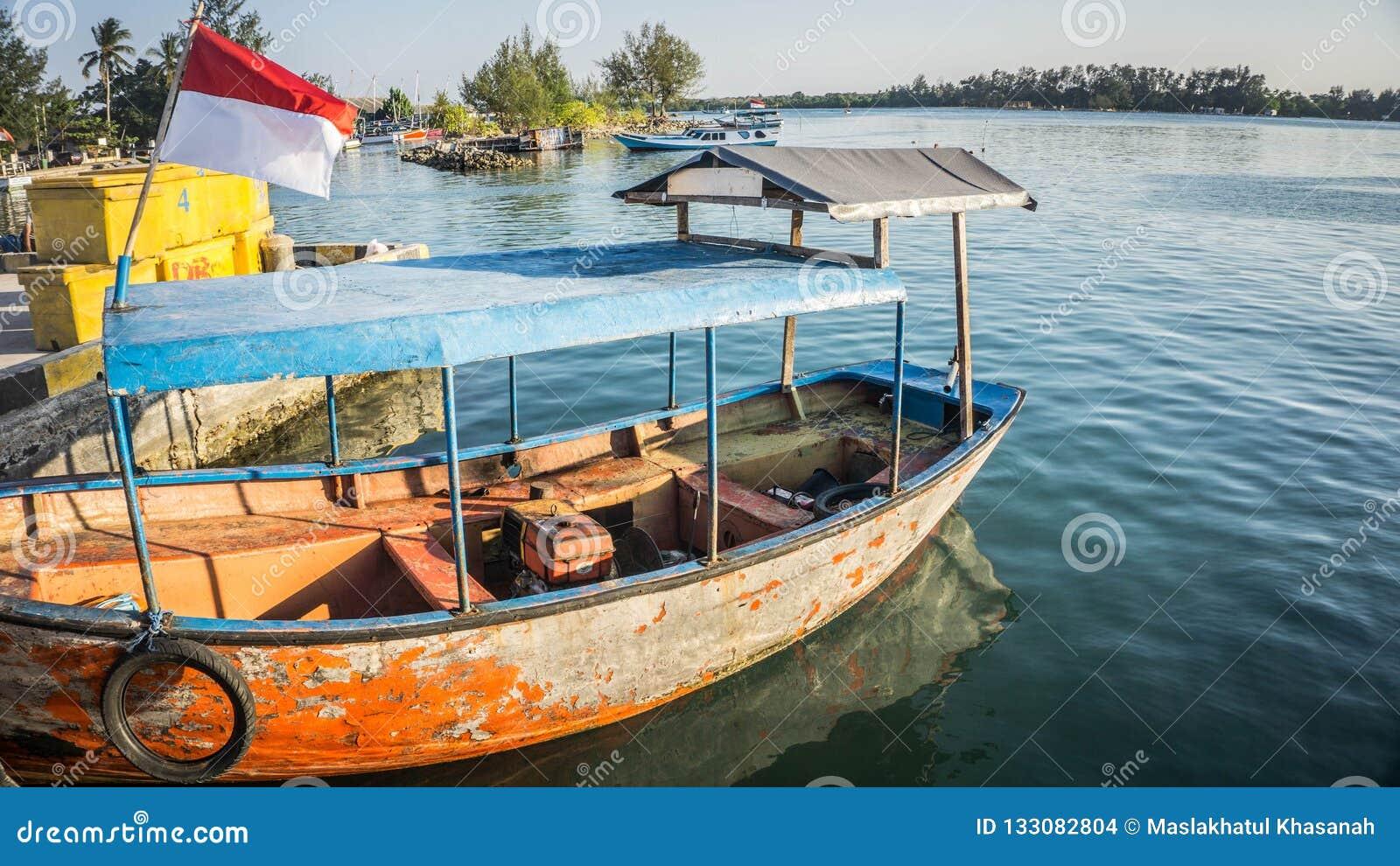 在岸蓝色海水的一条传统老小船与距离的绿色海岛在karimun jawa
