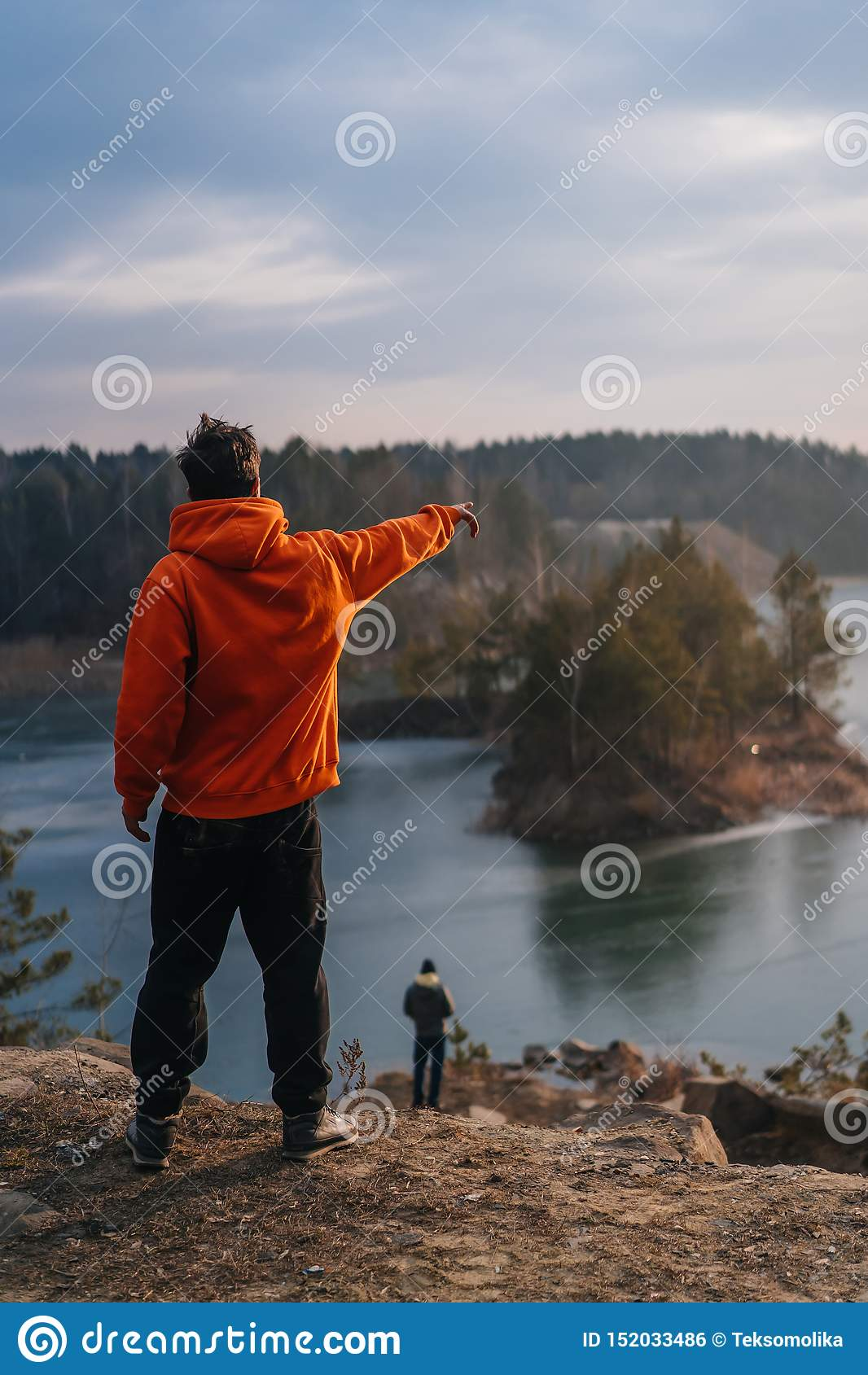 在峭壁边缘的一个年轻人身分为照相机摆在