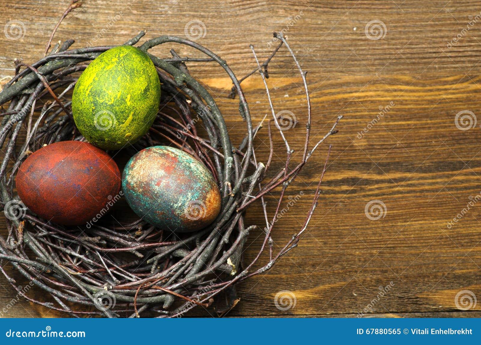 在巢的复活节彩蛋在木背景