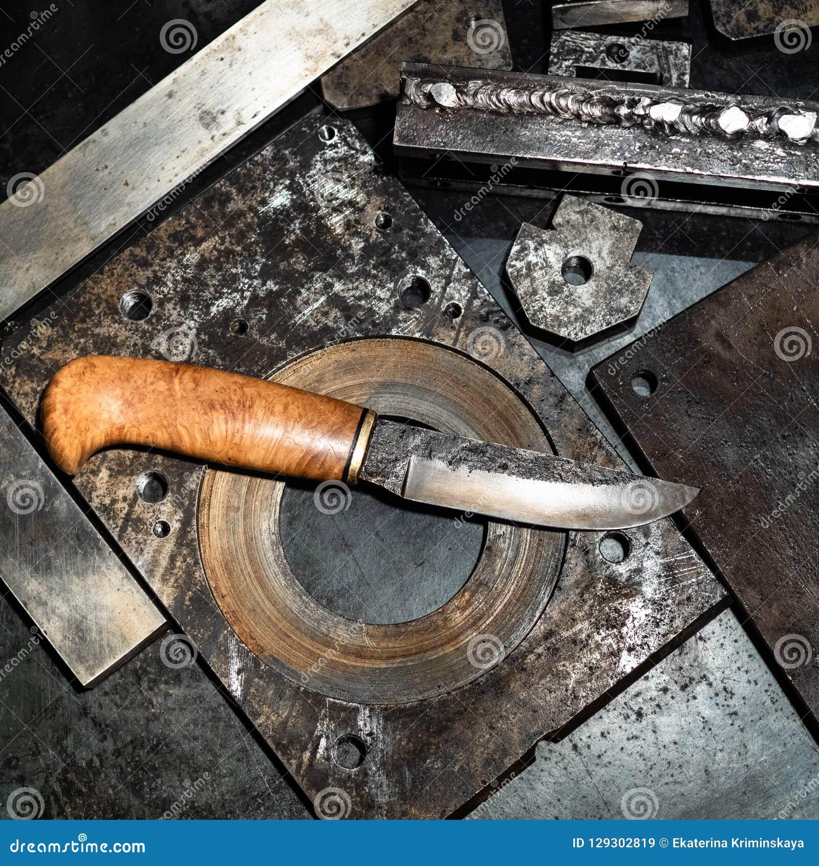 在工作凳的伪造的刀子在车床工厂车间