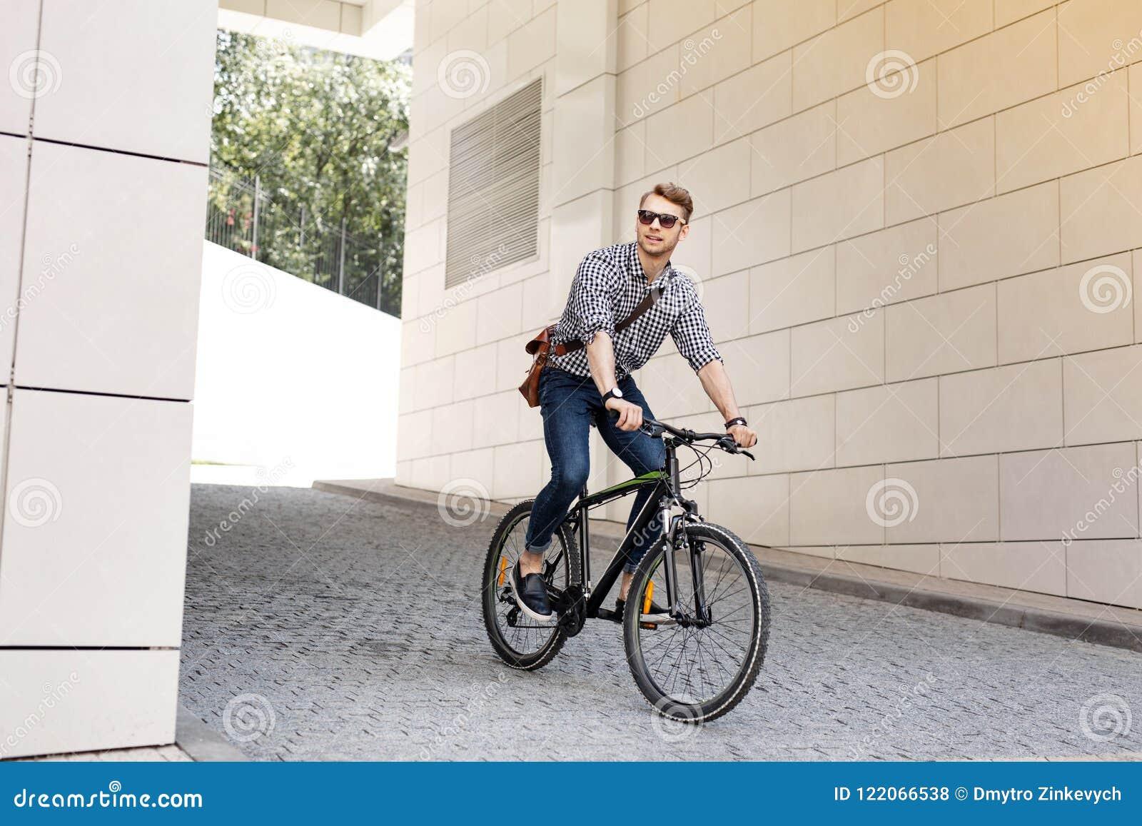 在工作的自行车的正面英俊的人骑马