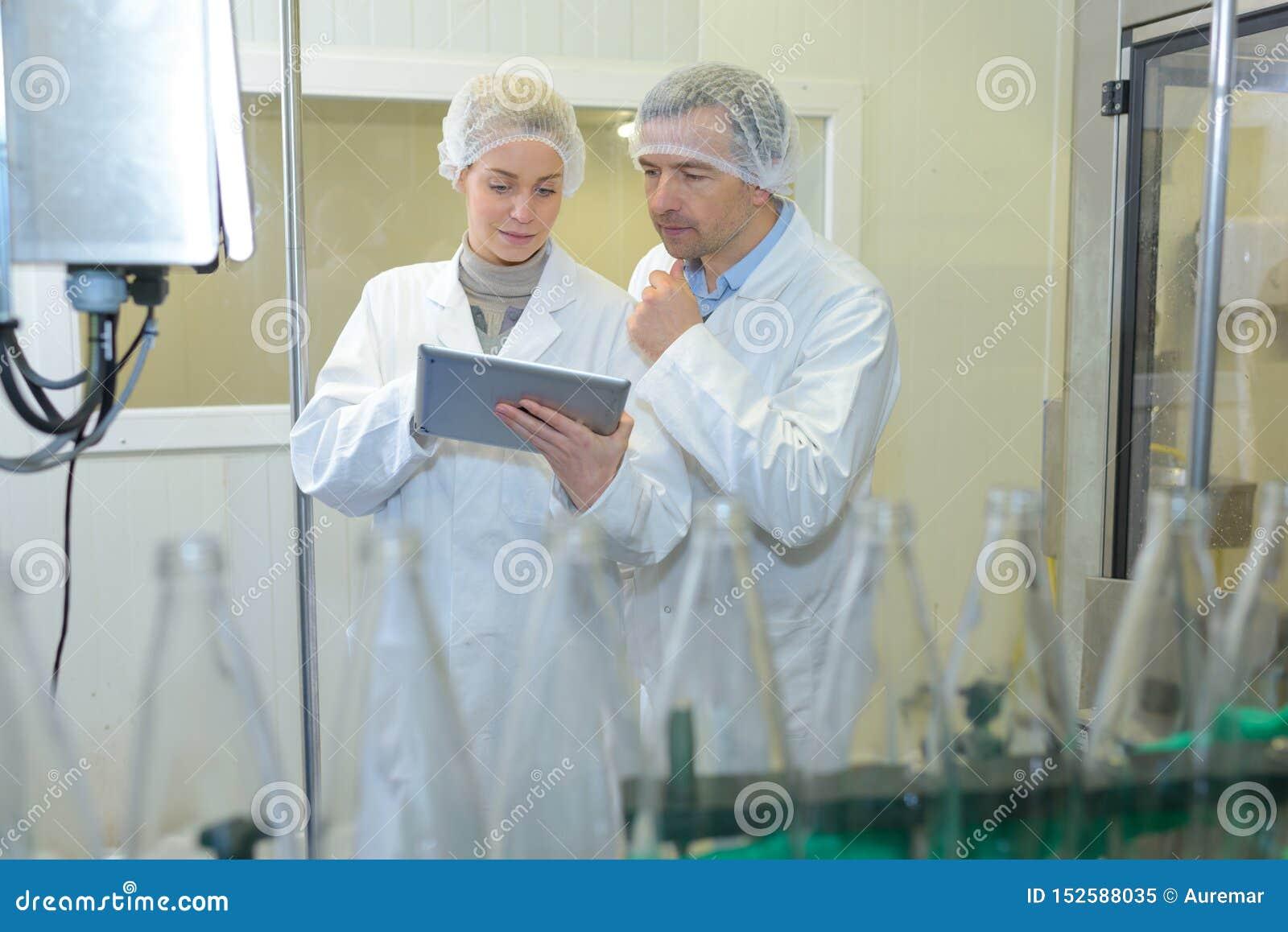 在工厂检查瓶的两位专家