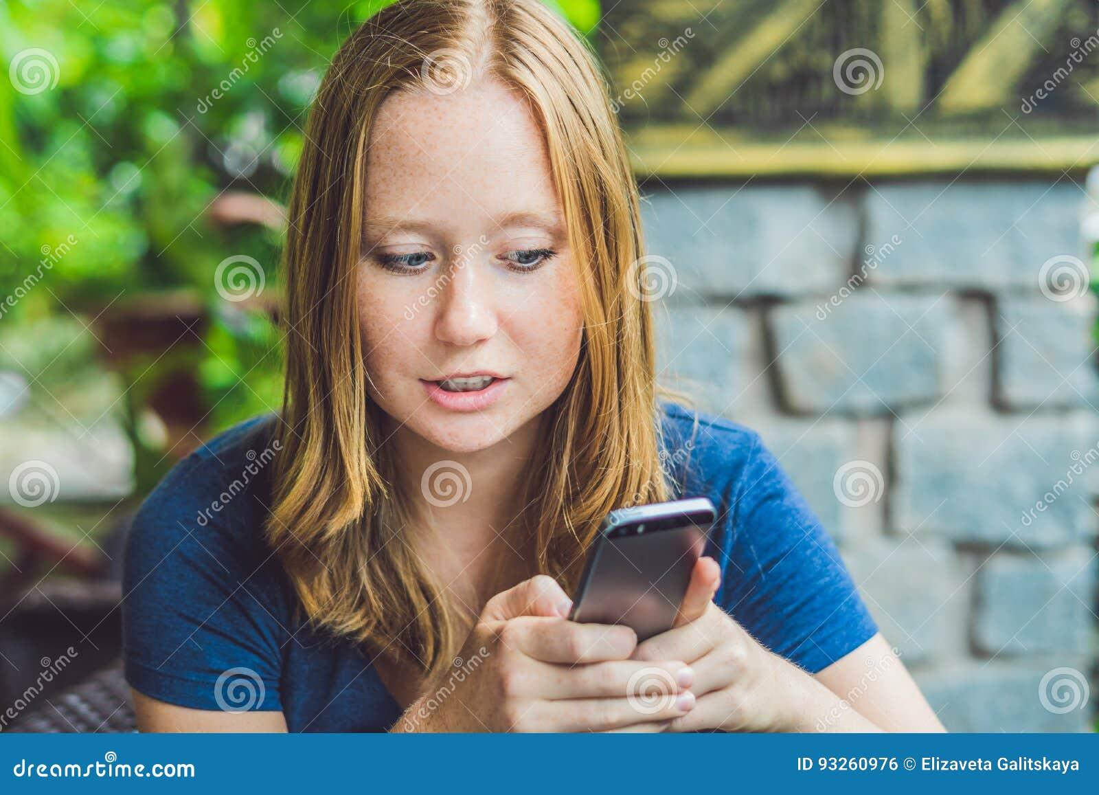 在巧妙的电话的妇女键入的正文消息在咖啡馆 15个妇女年轻人