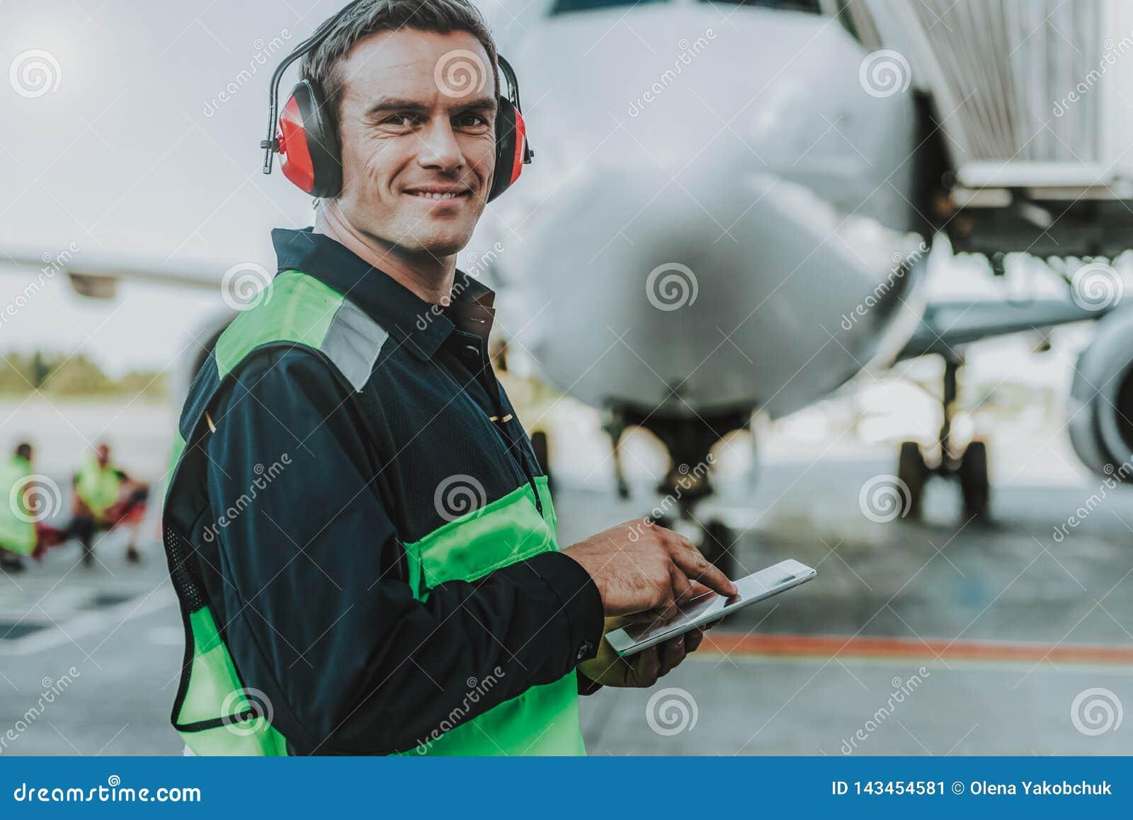 在巨大的飞机前面的微笑的英俊的工作者身分