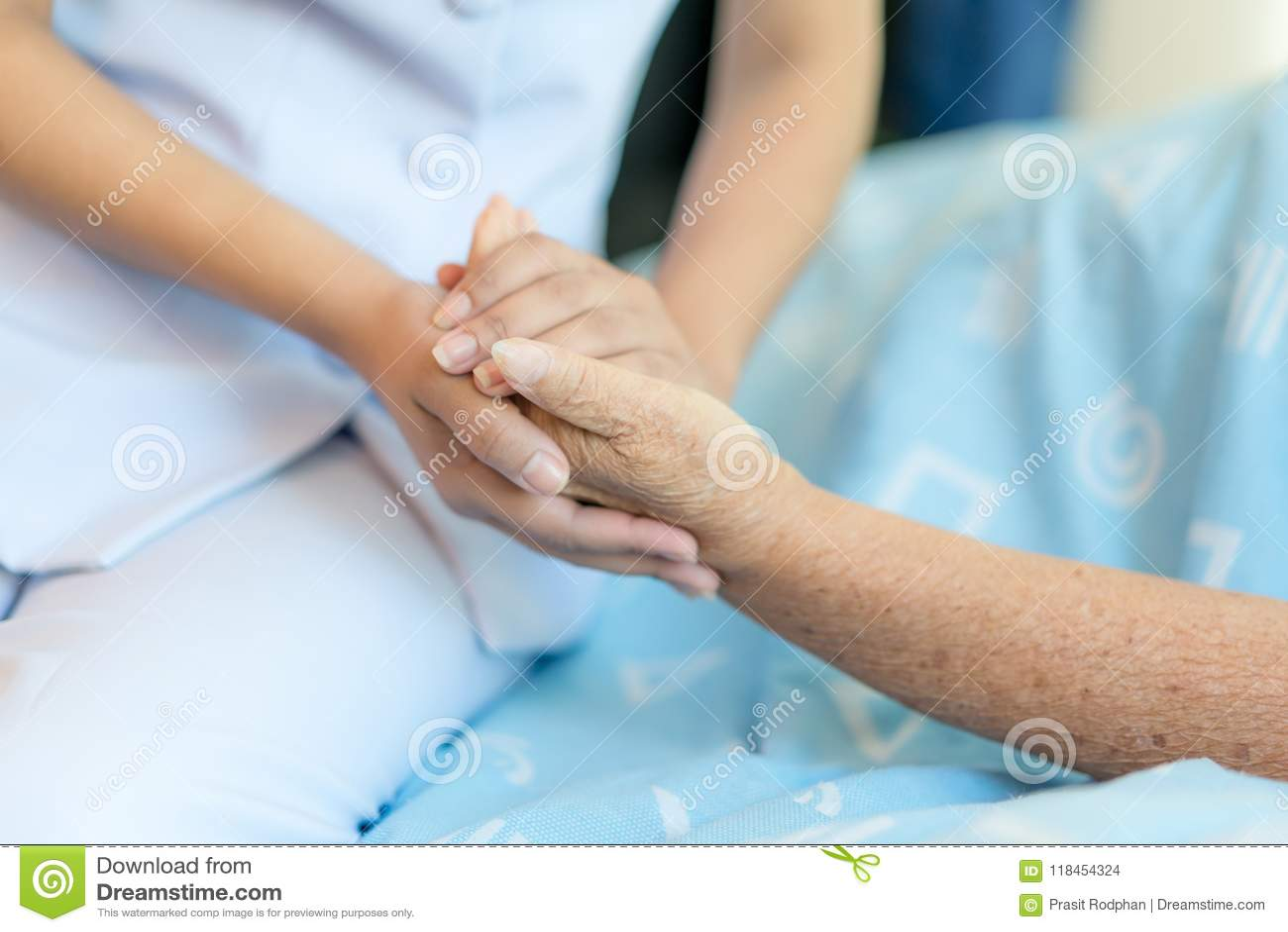 在帮助h的一个老妇人旁边护理坐医院病床