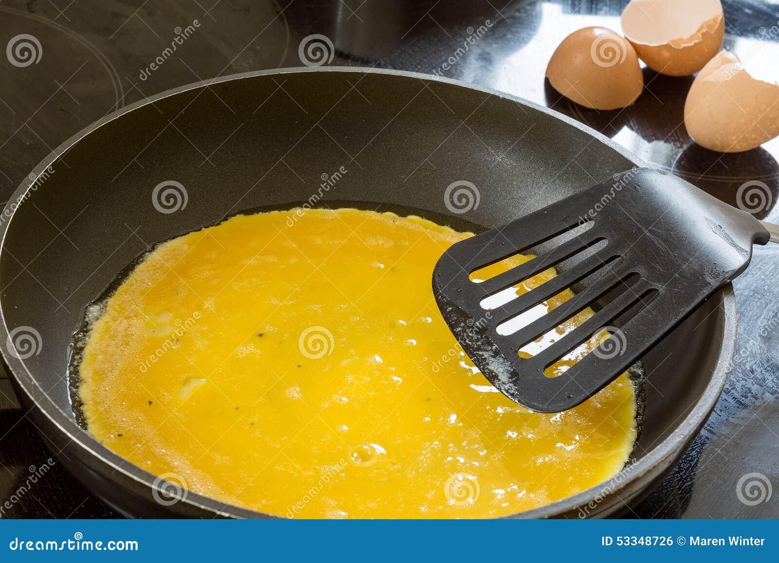 在平底锅的液体鸡蛋薄煎饼或炒蛋的