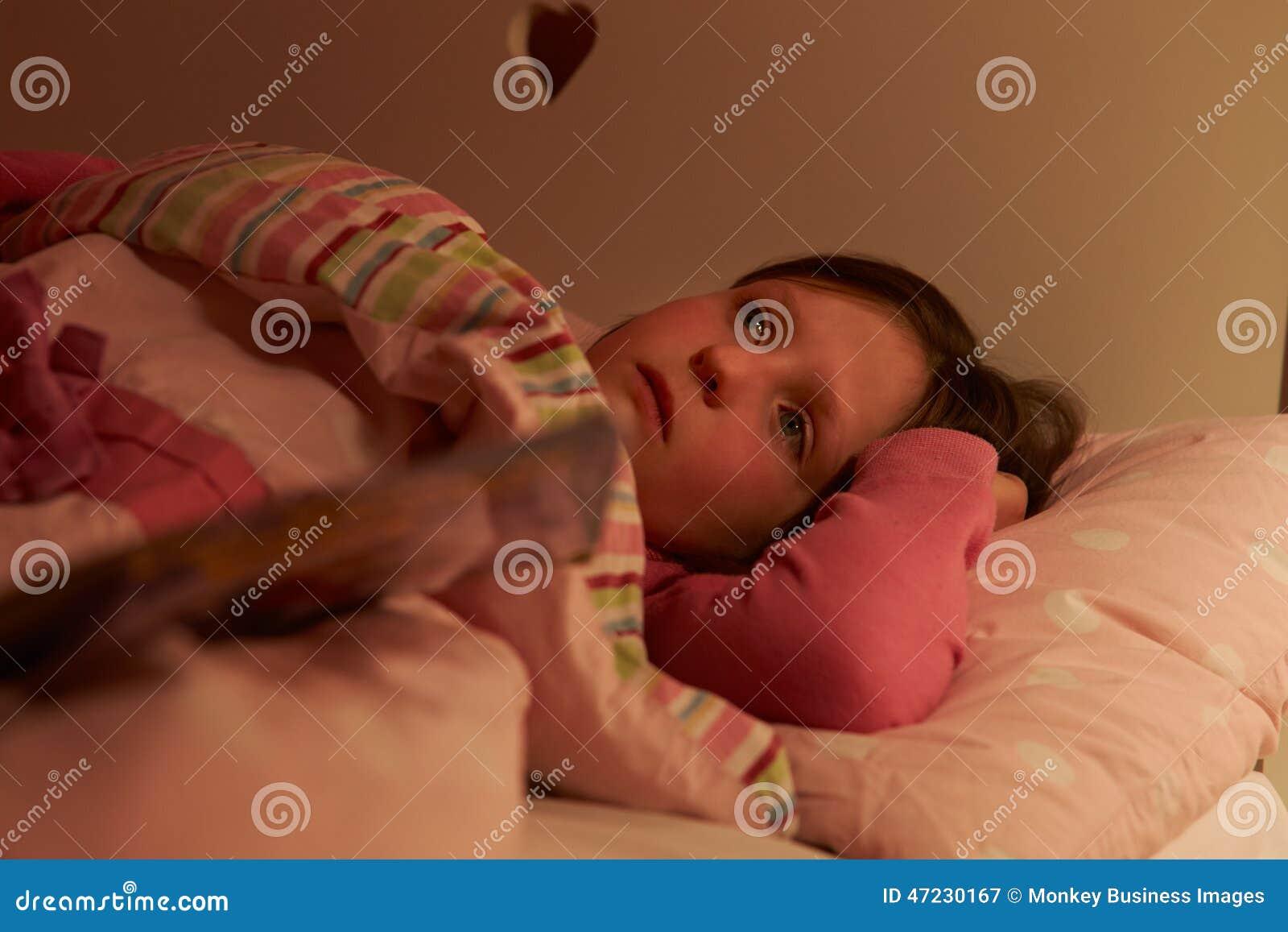 在床上的担心的女孩醒在晚上