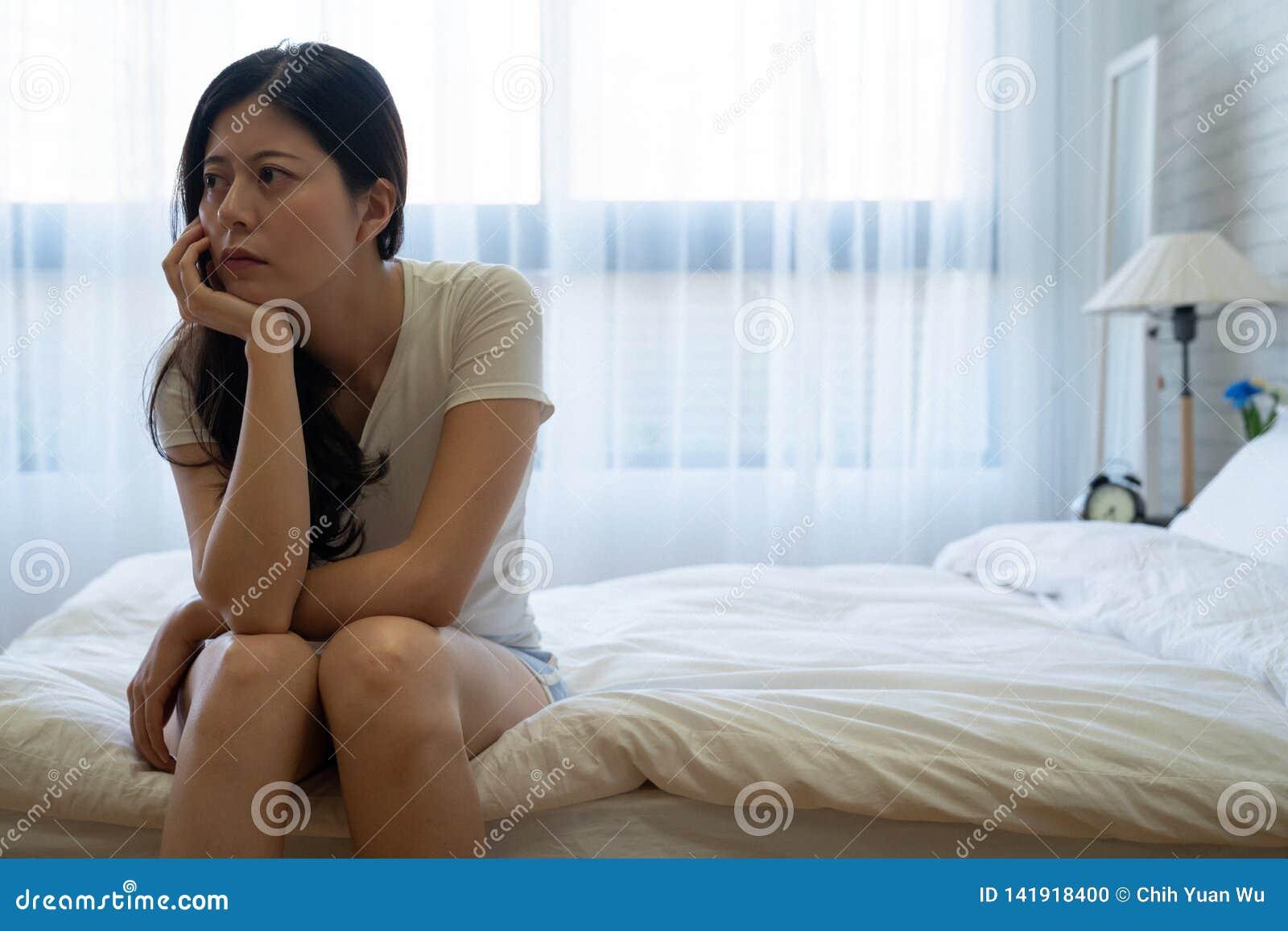 在床上的沮丧的妇女考虑关于问题