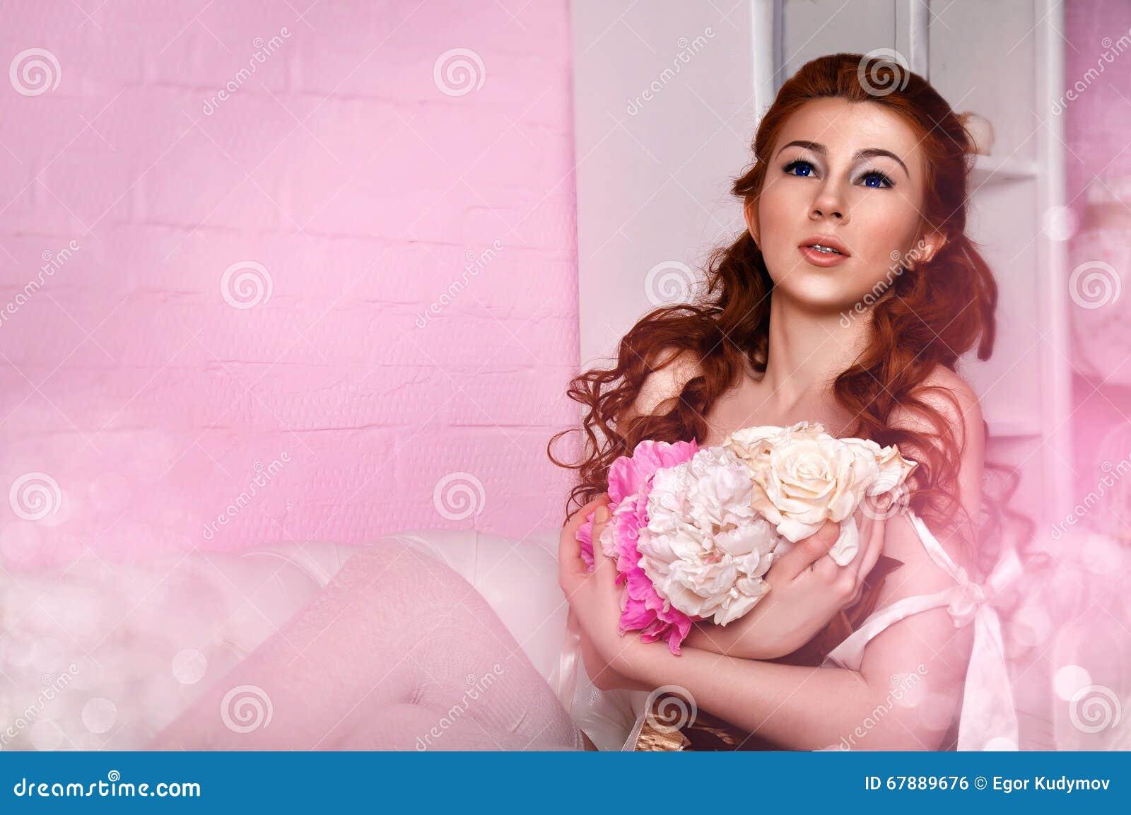 在床上的美好的少妇佩带的白色女用贴身内衣裤