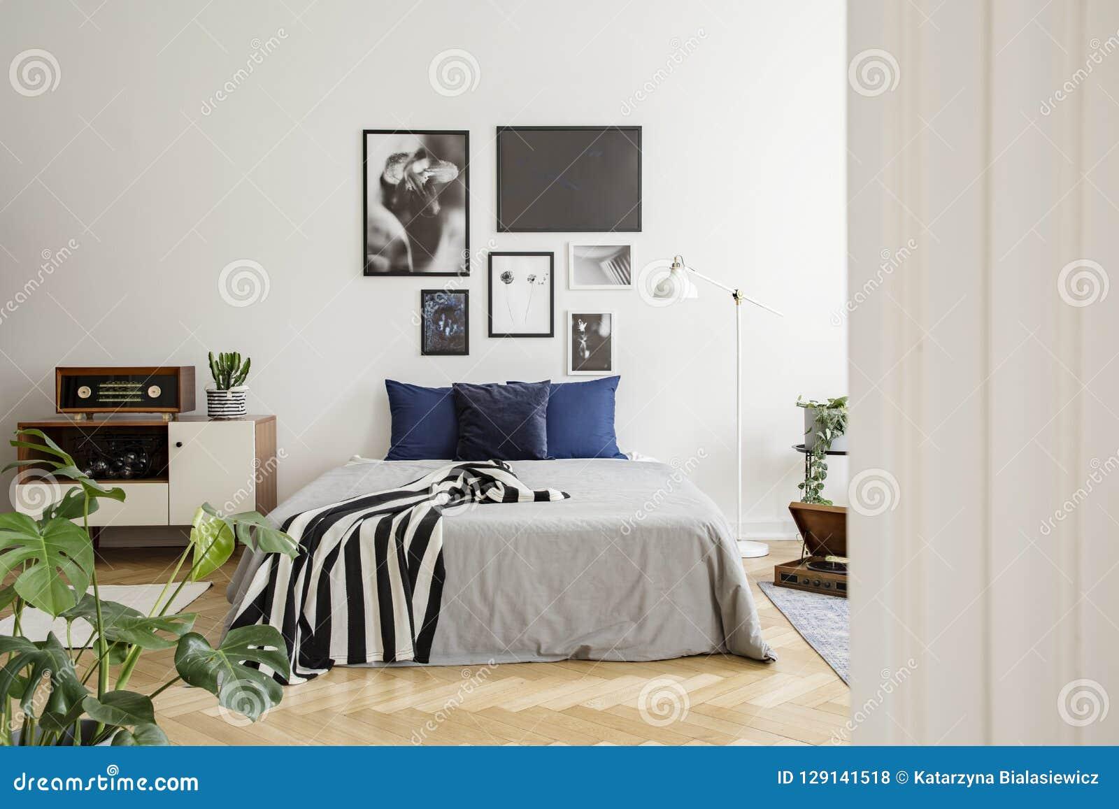 在床旁边的白色木洗脸台与深蓝枕头、灰色鸭绒垫子和镶边的黑白毯子在卧室