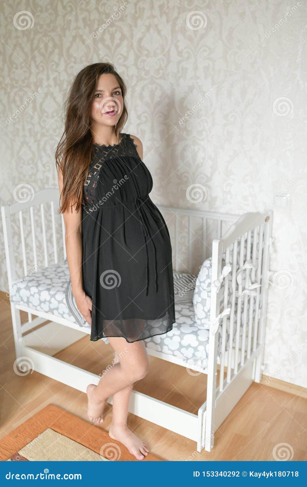 在床附近的怀孕的女孩孩子的 孩子的kravatka白色 为孩子的诞生做准备 a??