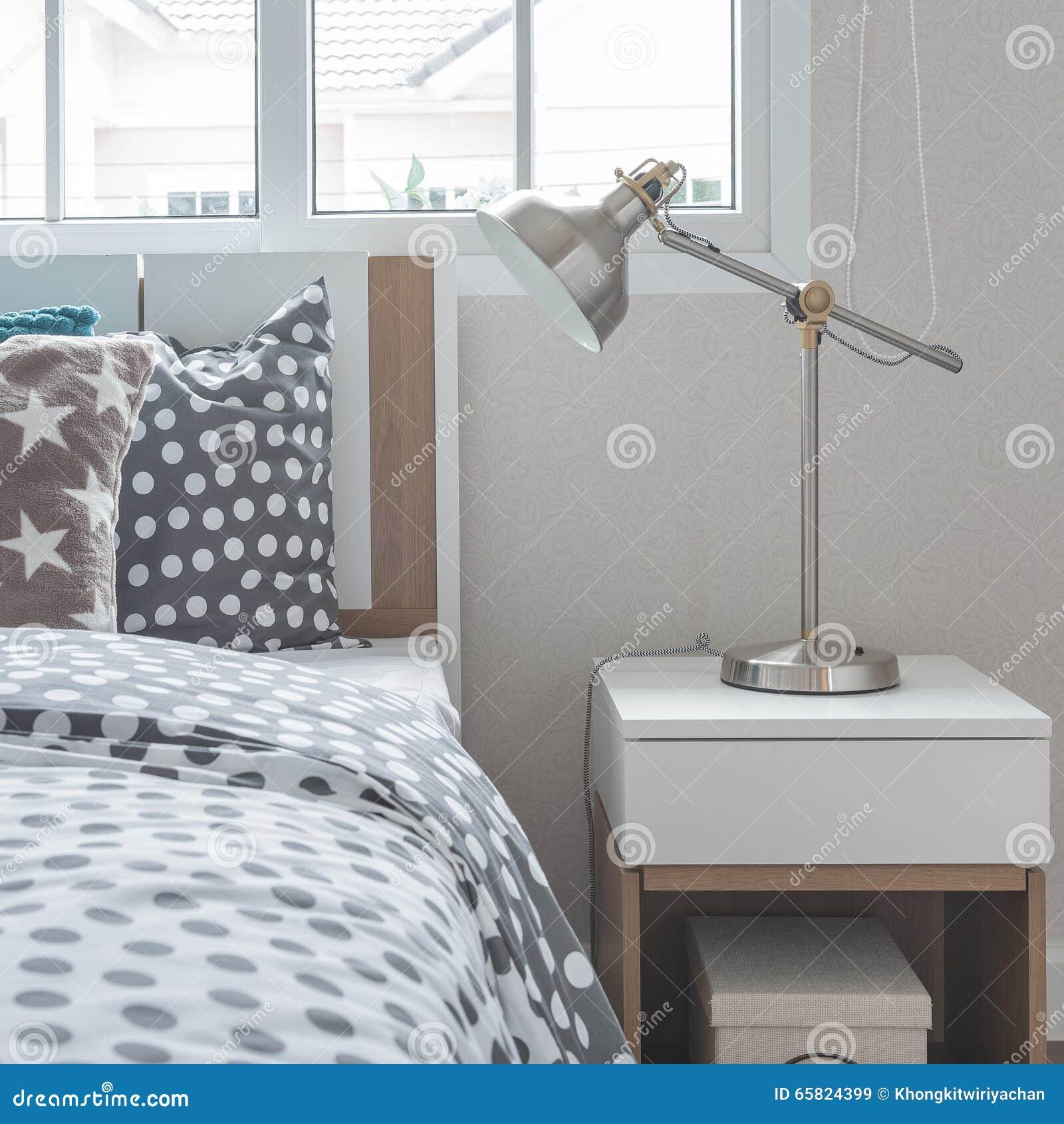 在床头柜的现代灯与木床图片