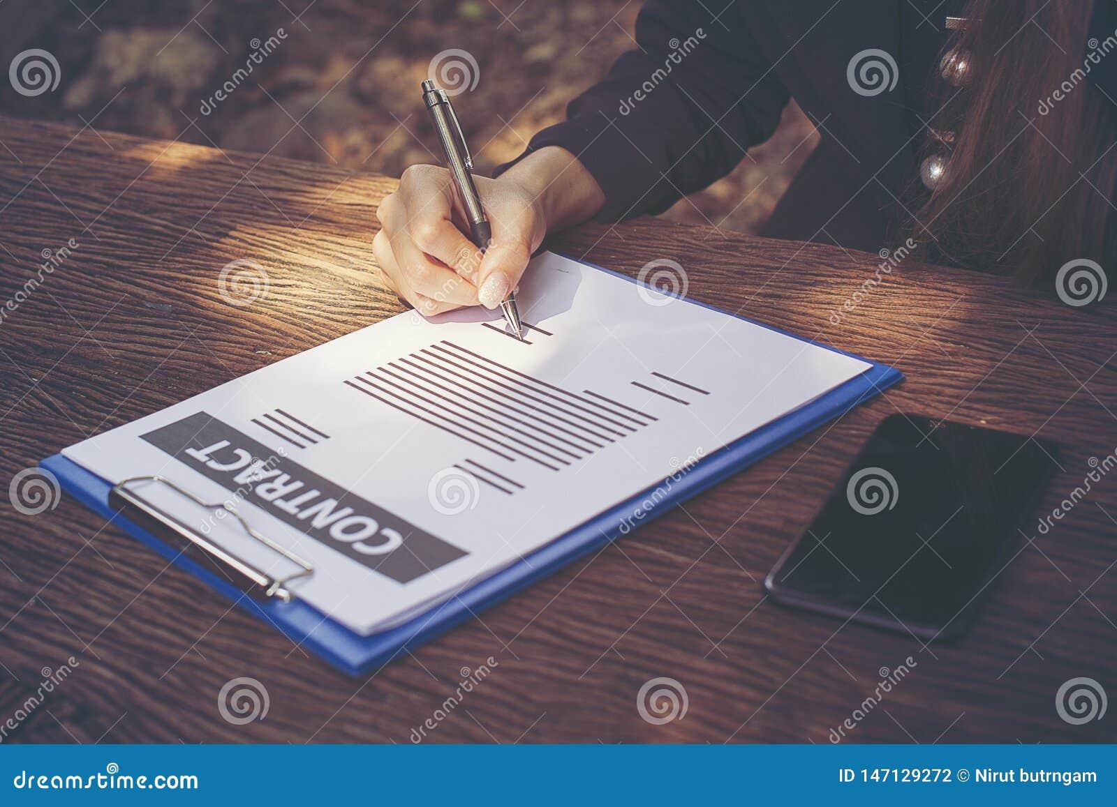 在庭院书桌上的女商人签署的合同文件