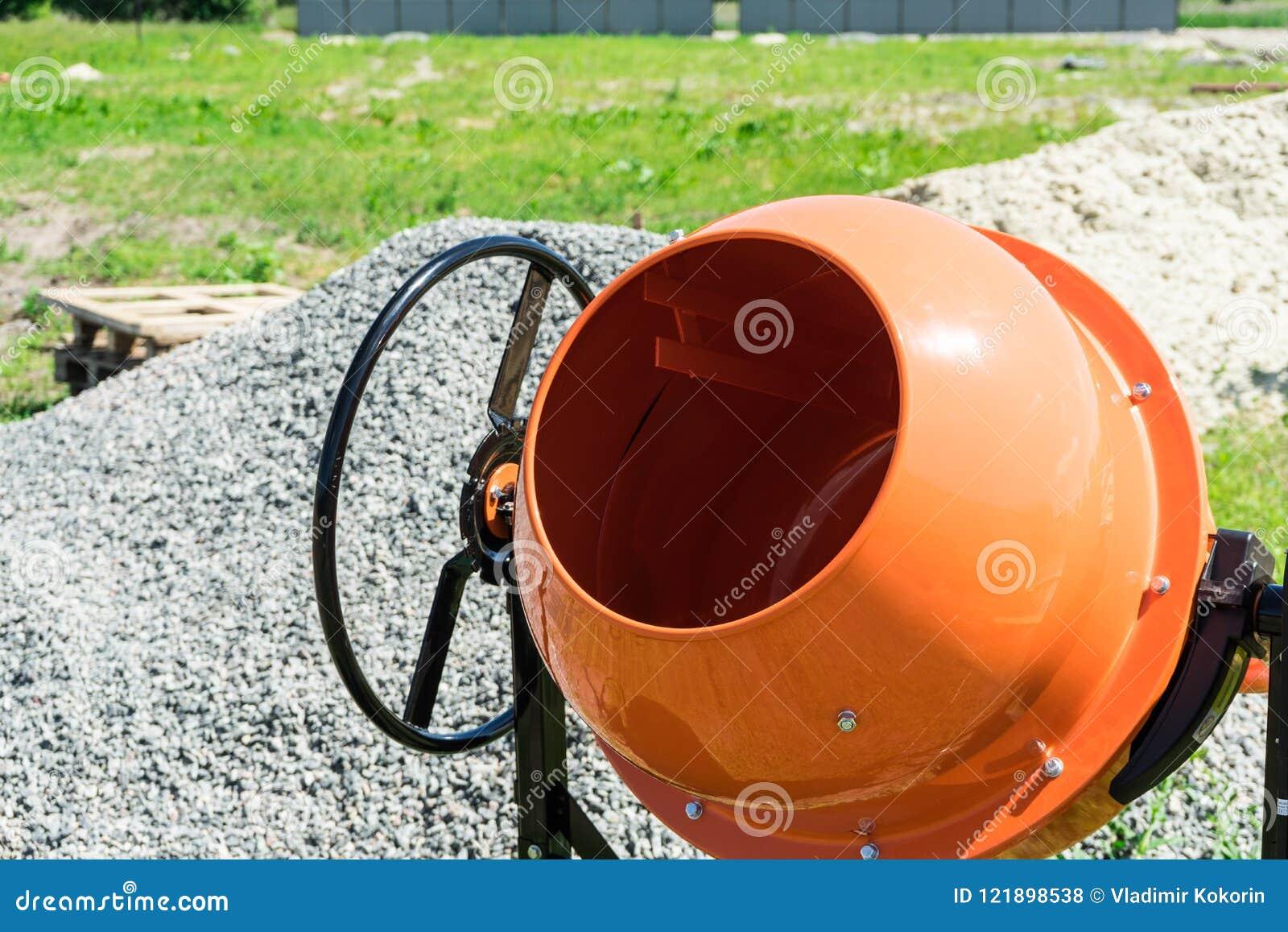 在建造场所安装的照片混凝土搅拌机在堆沙子和石渣旁边